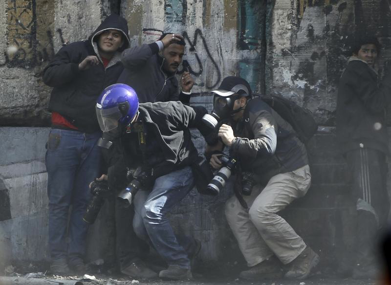 Photographers cower as protesters throw stones towards riot police along Sheikh Rihan street near Tahrir Square in Cairo January 25, 2013.