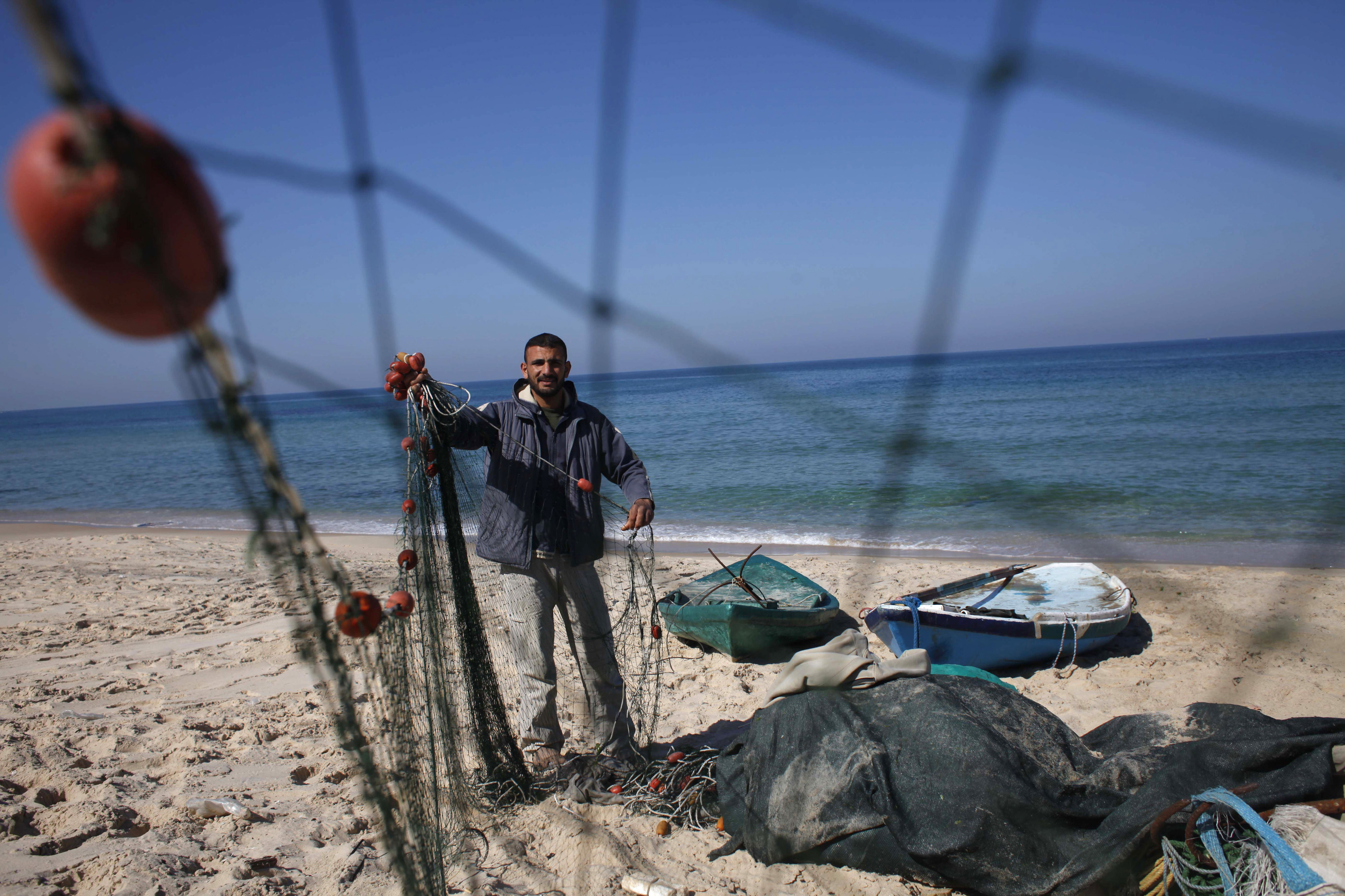 Palestinian fisherman Joudat Ghrab, who said he scooped a 500-kg bronze statue of the Greek God Apollo from the sea bed last August, prepares his fishing net on the beach of Deir El-Balah in the central Gaza Strip February 9, 2014.