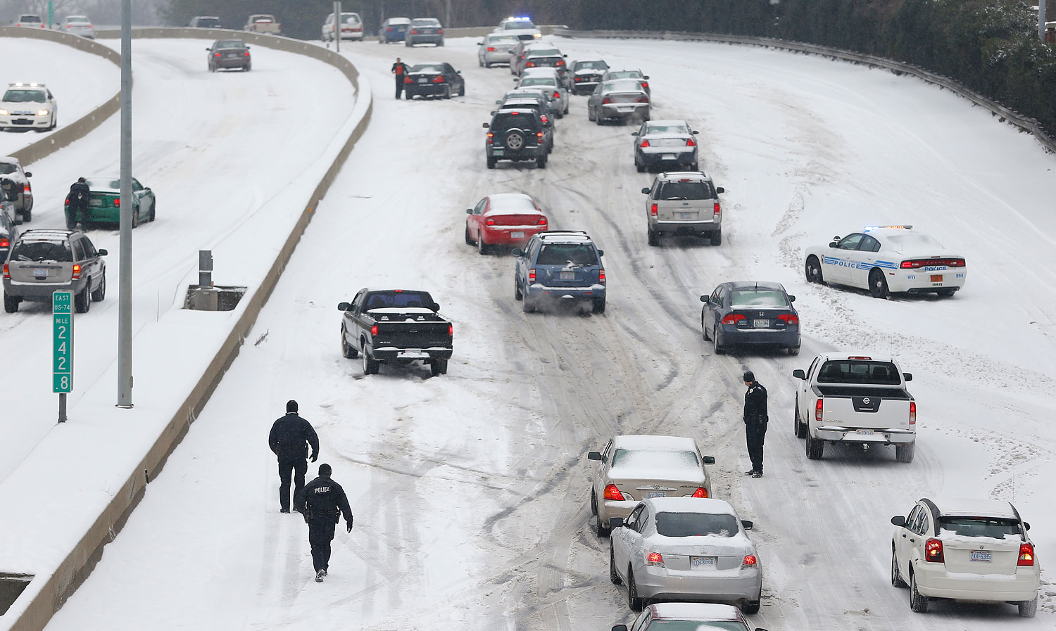 Charlotte Mecklenburg Police Officers work to assist motorists as they attempt to drive up a hill that is covered in snow in Charlotte, North Carolina Feb. 12, 2014.