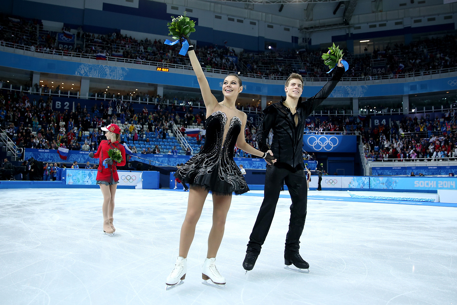 Gold Medalists Yulia Lipnitskaya, Elena Ilinykh and Nikita Katsalapov of Russia skate after the flower ceremony for the Team Figure Skating Overall during day two of the Sochi 2014 Winter Olympics at Iceberg Skating Palace on February 9, 2014 in Sochi, Russia.