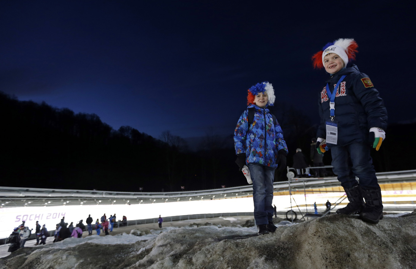 Children wait for the start of the final run during the men's doubles luge at the 2014 Winter Olympics, on Feb. 12, 2014, in Krasnaya Polyana, Russia.