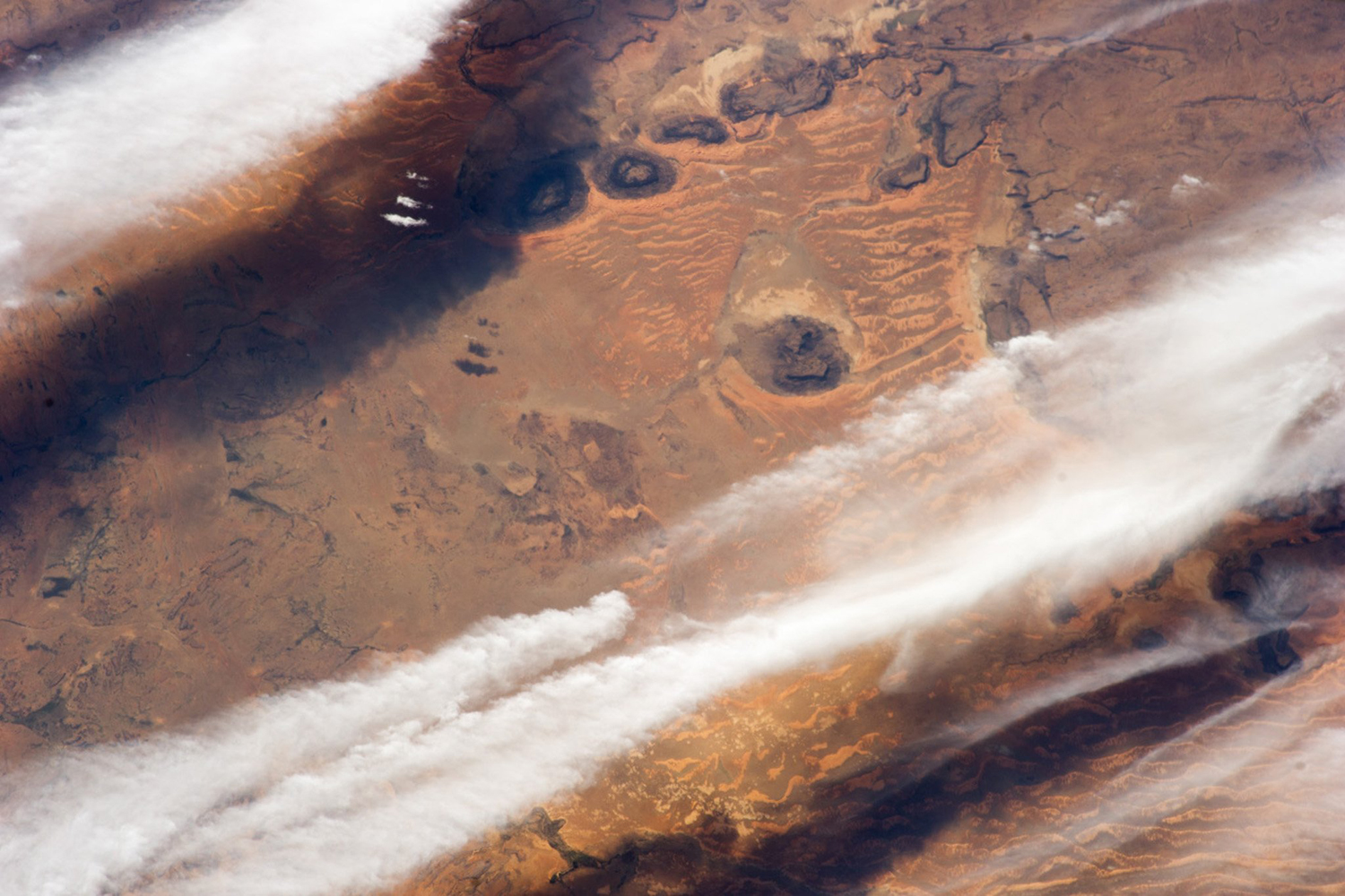 This NASA photograph of cloud bands over southern Mauritania was obtained Jan. 28, 2014, and taken by the crew of the International Space Station. Prevailing winds in this part of the Sahara Desert blow from the northeast. The sand that makes the wavy dunes is blown in from a zone immediately upwind, where dry river beds and dry lakes provide plenty of raw material.
