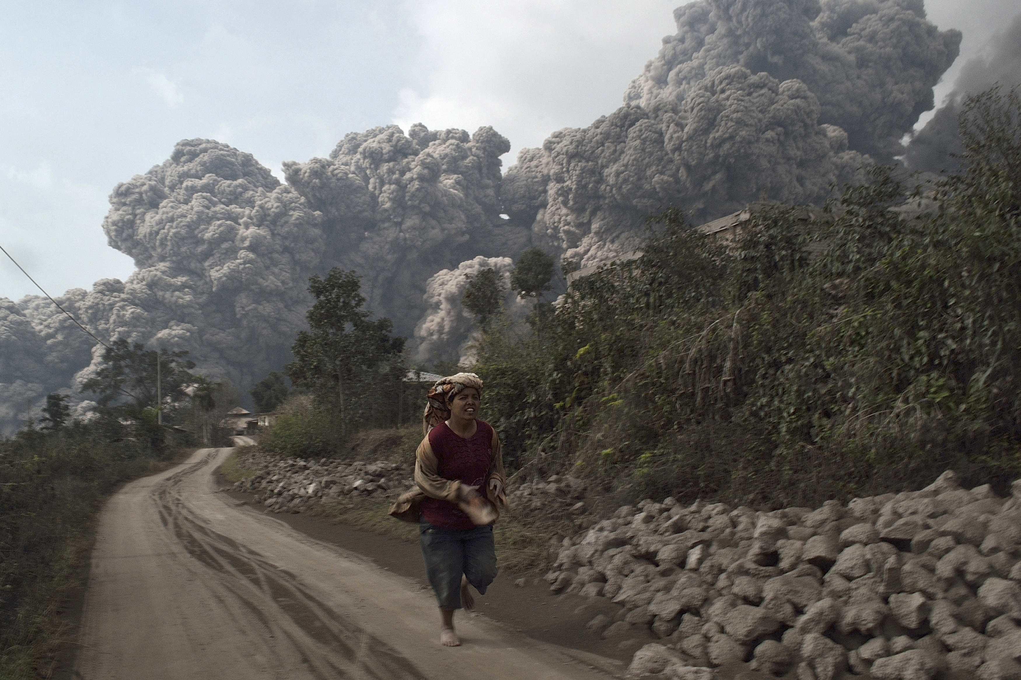 A villager run as Mount Sinabung erupt at Sigarang-Garang village in Karo district, Indonesia's North Sumatra province, Feb. 1, 2014.