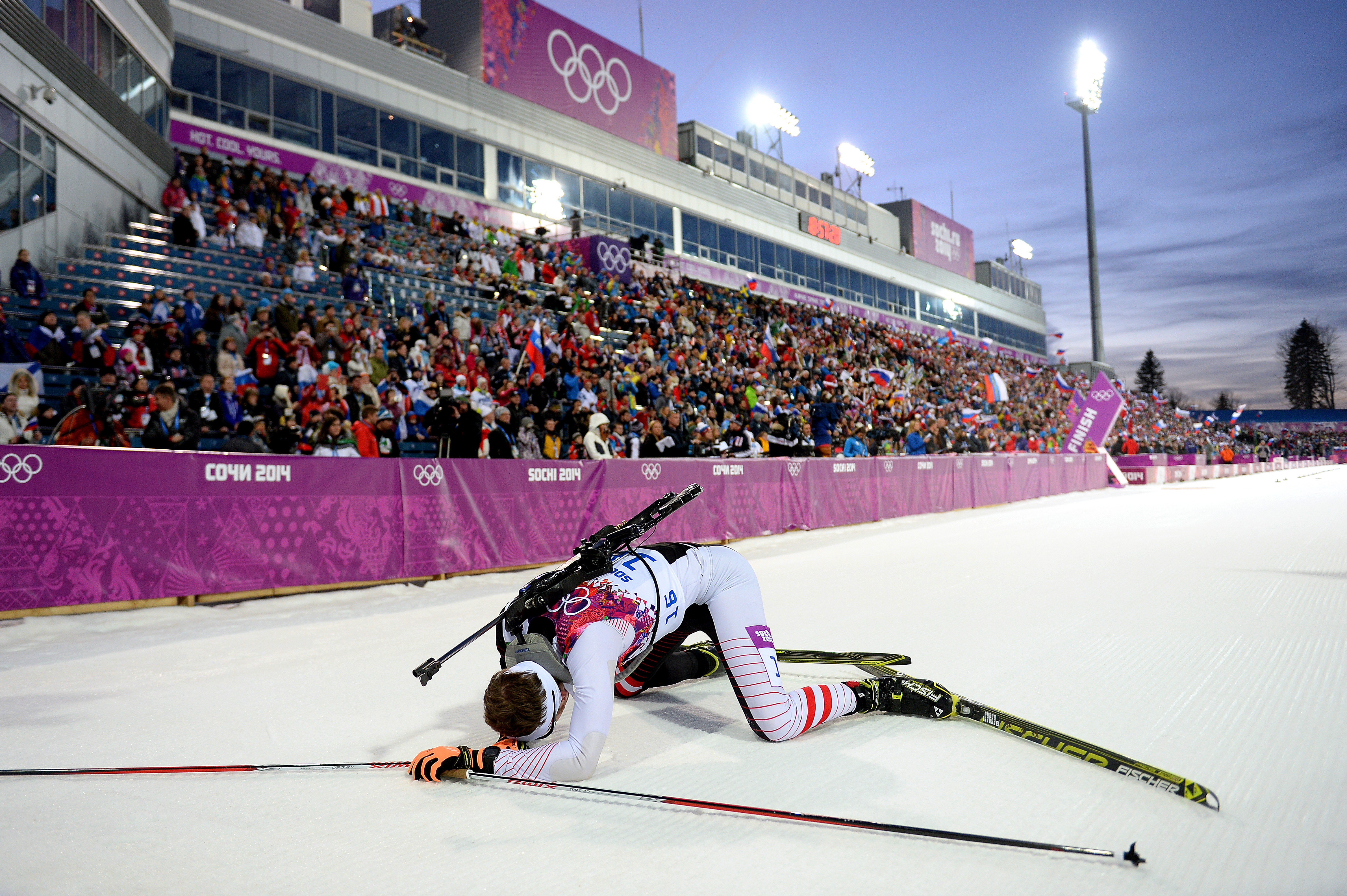 Simon Eder of Austria collapses in the snow after the Men's Individual 20 km.