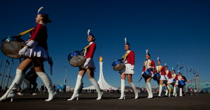 Cheerleaders walk to a venue past the burning Olympic cauldron during the 2014 Winter Olympics in Sochi, Russia, Feb. 13, 2014.