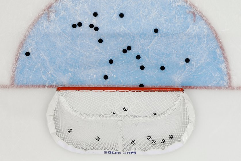 Pucks litter the ice around the net after Team USA warms up before their game against Slovakia during the men's ice hockey game at Shayba Arena.