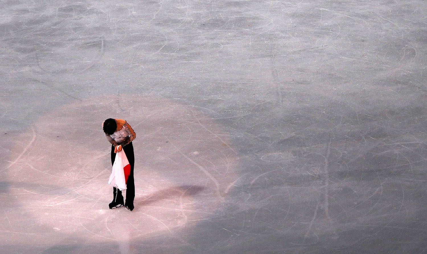 First-placed Japan's Yuzuru Hanyu bows after the flower ceremony for the figure skating men's free skating program.