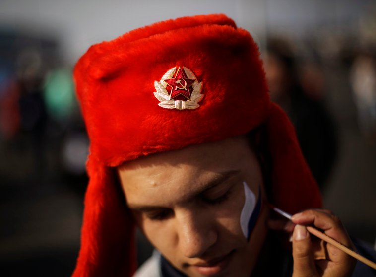 An emblem with the Soviet hammer and sickle decorates the hat of Serdar Yuldashev as he has his face painted in the colors of the Russian flag.