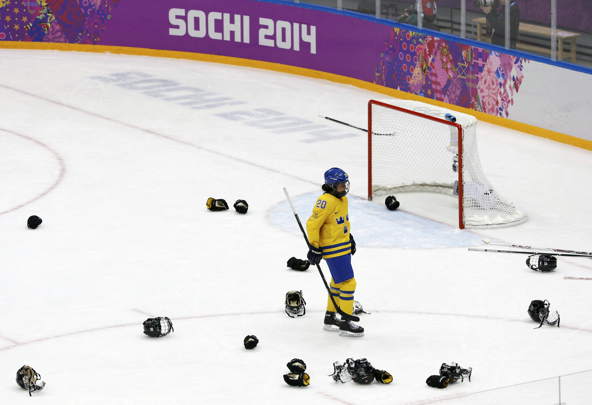 Sweden's Fanny Rask skates through the helmets and gloves of Switzerland's celebrating players at the end of their women's ice hockey bronze medal game.