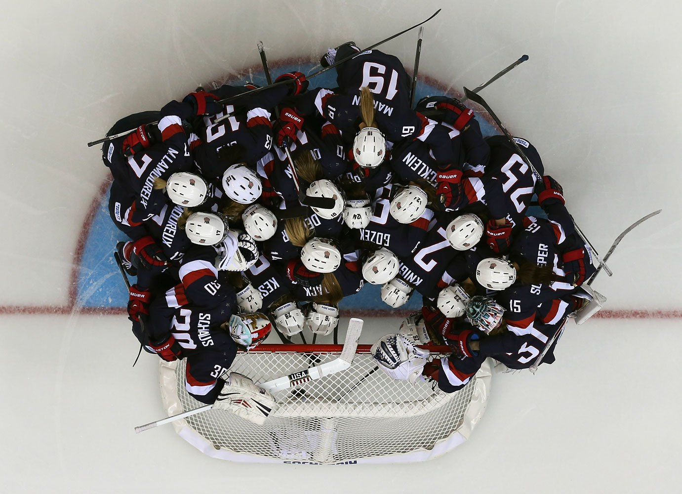Members of USA's women's ice hockey team huddle around USA's goalie Molly Schaus before their women's preliminary round hockey game against Switzerland at the Sochi 2014 Winter Olympic Games Feb. 10, 2014.