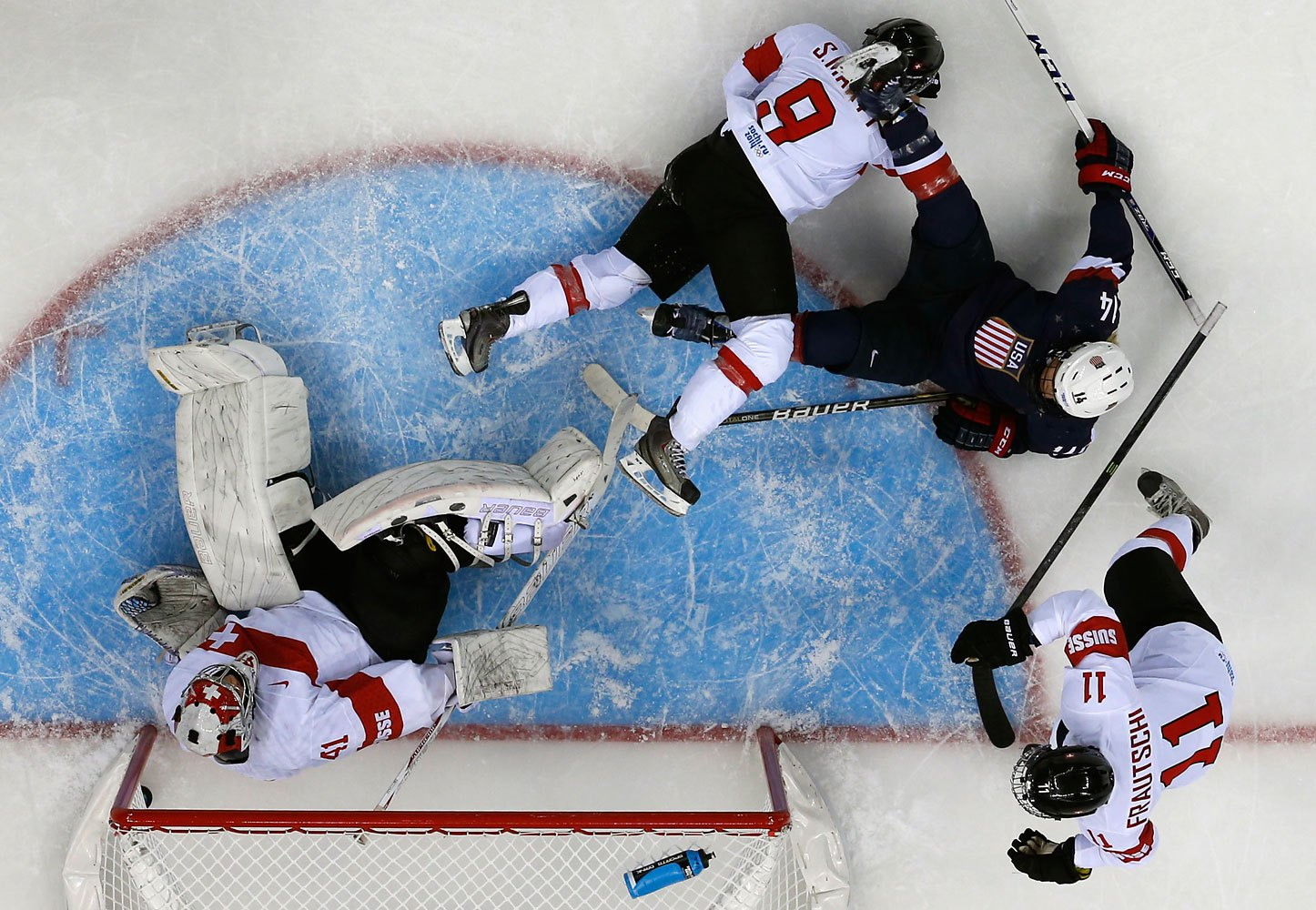The puck sits in the net behind Switzerland's goalie Florence Schelling after a goal by Team USA's Amanda Kessel (not seen), during the first period of their women's preliminary round hockey game at the Sochi 2014 Winter Olympic Games Feb. 10, 2014.