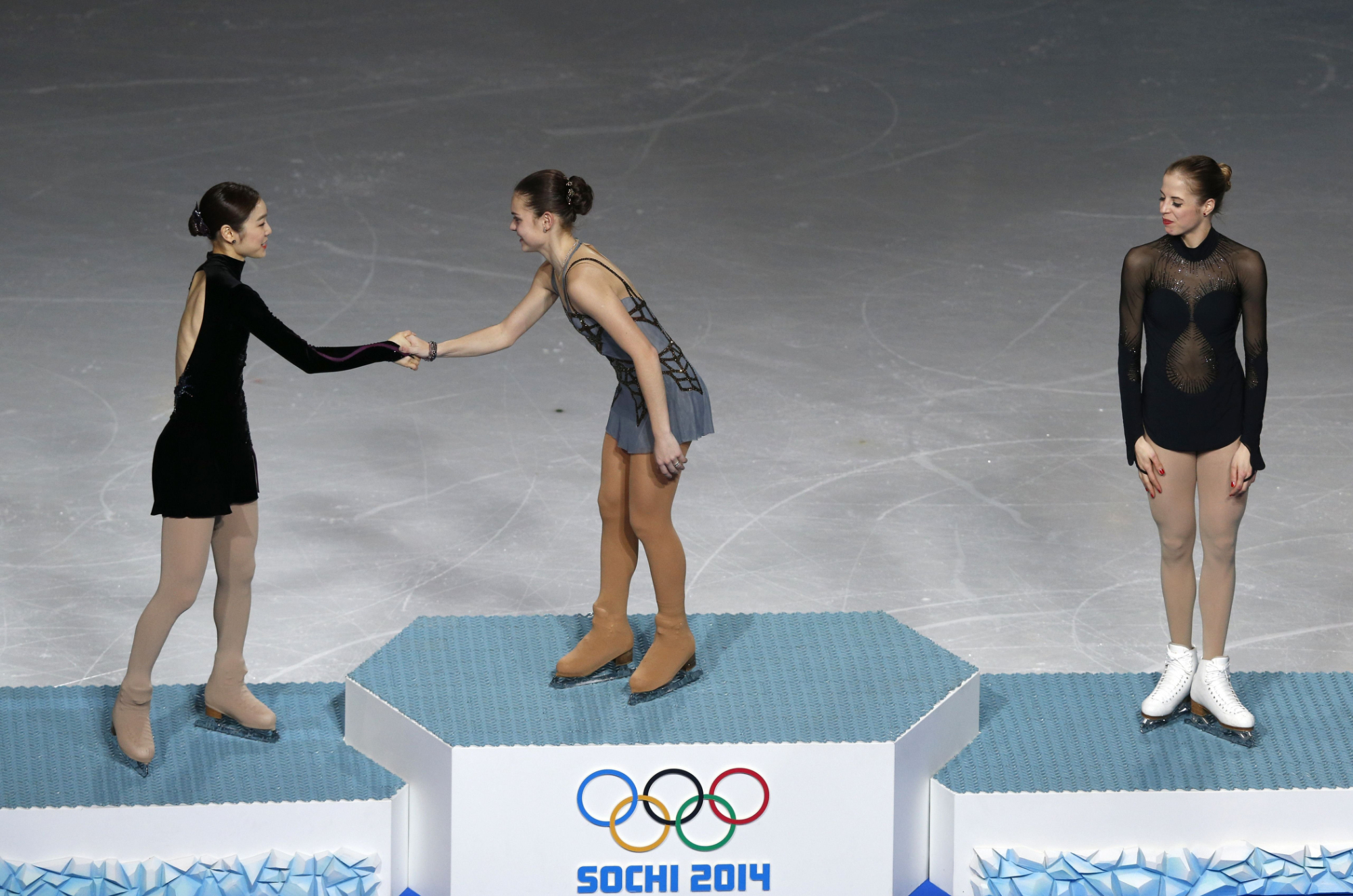 (From L) South Korea's silver medalist Kim Yu-Na, Russia's gold medalist Adelina Sotnikova and Italy's bronze medalist Carolina Kostner celebrate on the podium during the Women's Figure Skating Flower Ceremony.