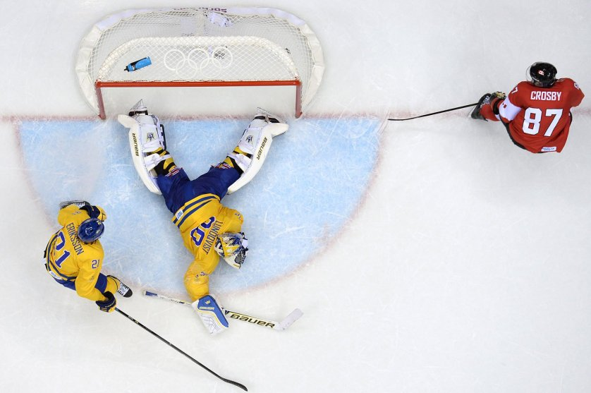 Canada's Sidney Crosby (R) scores in the nets of Sweden's goalkeeper Henrik Lundqvist as Sweden's Loui Eriksson looks on during the Men's ice hockey final Sweden vs Canada.