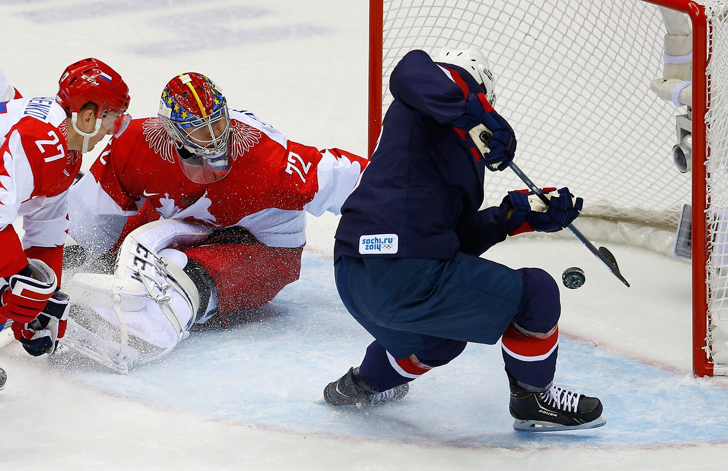 Team USA's Cam Fowler, right, scores on Russia's goalie Sergei Bobrovski and Russia's Alexei Tereshenko during the second period of their men's preliminary round ice hockey game.