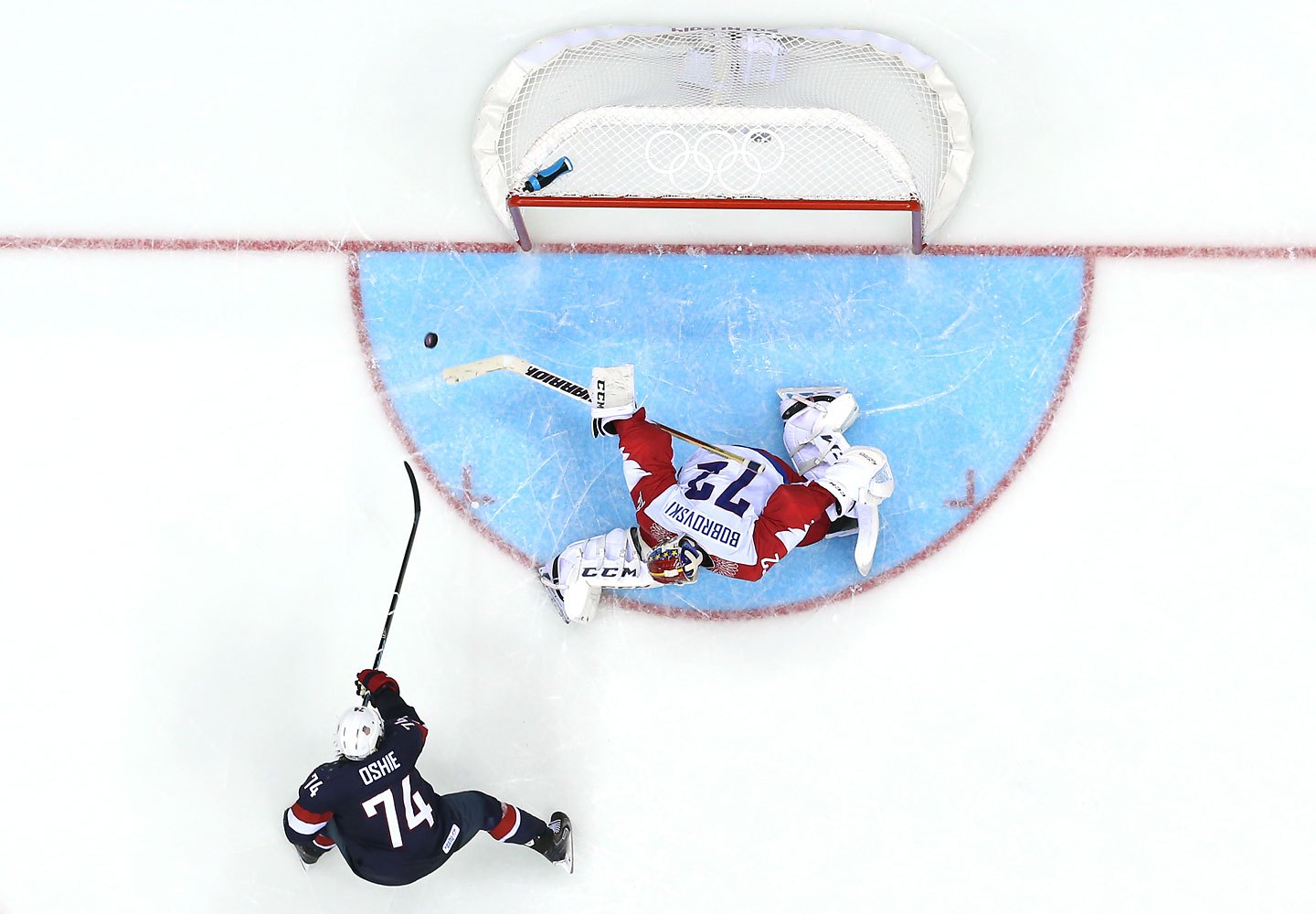 .J. Oshie #74 of the United States shoots during a shootout against Sergei Bobrovski #72 of Russia .