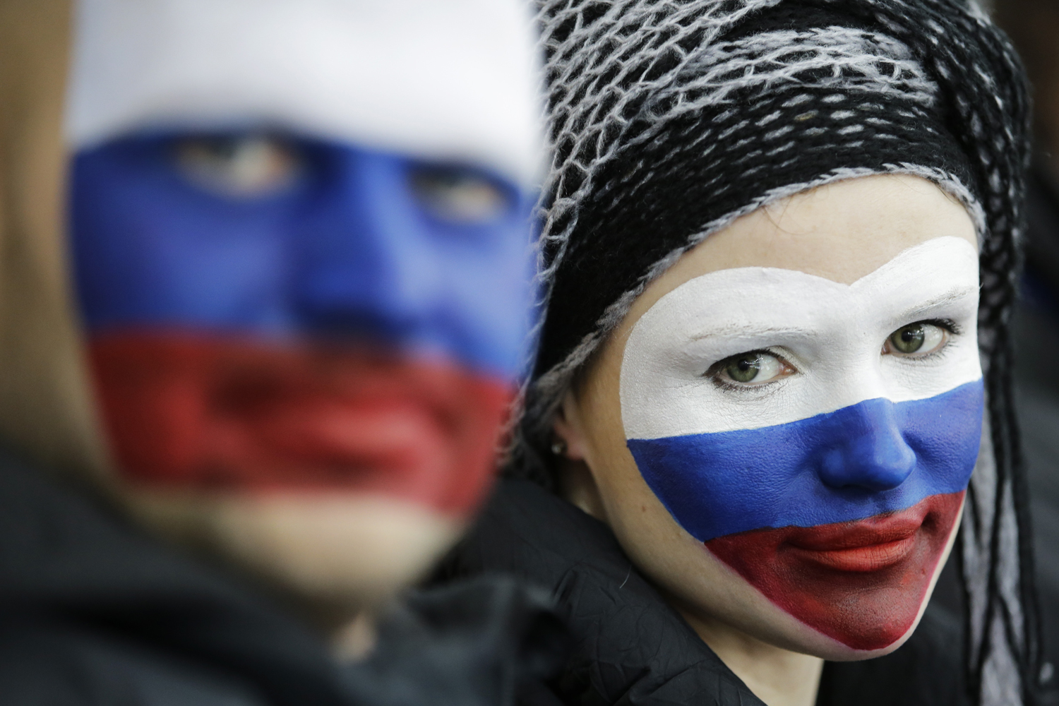 Russian skating fans, faces painted with the colors of their national flag, wait for the start of the women's 1,500-meter speedskating race at the Adler Arena Skating Center during the 2014 Winter Olympics, Sunday, Feb. 16, 2014, in Sochi, Russia.
