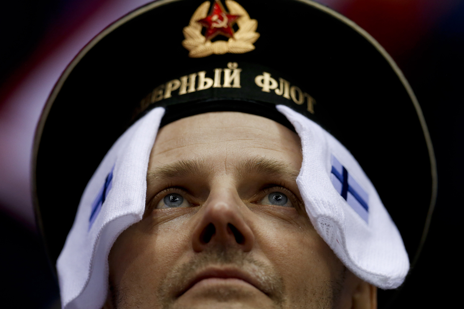 A hockey fan wears symbols from the Finnish flag before a men's ice hockey game against Canada at the 2014 Winter Olympics, Sunday, Feb. 16, 2014, in Sochi, Russia.