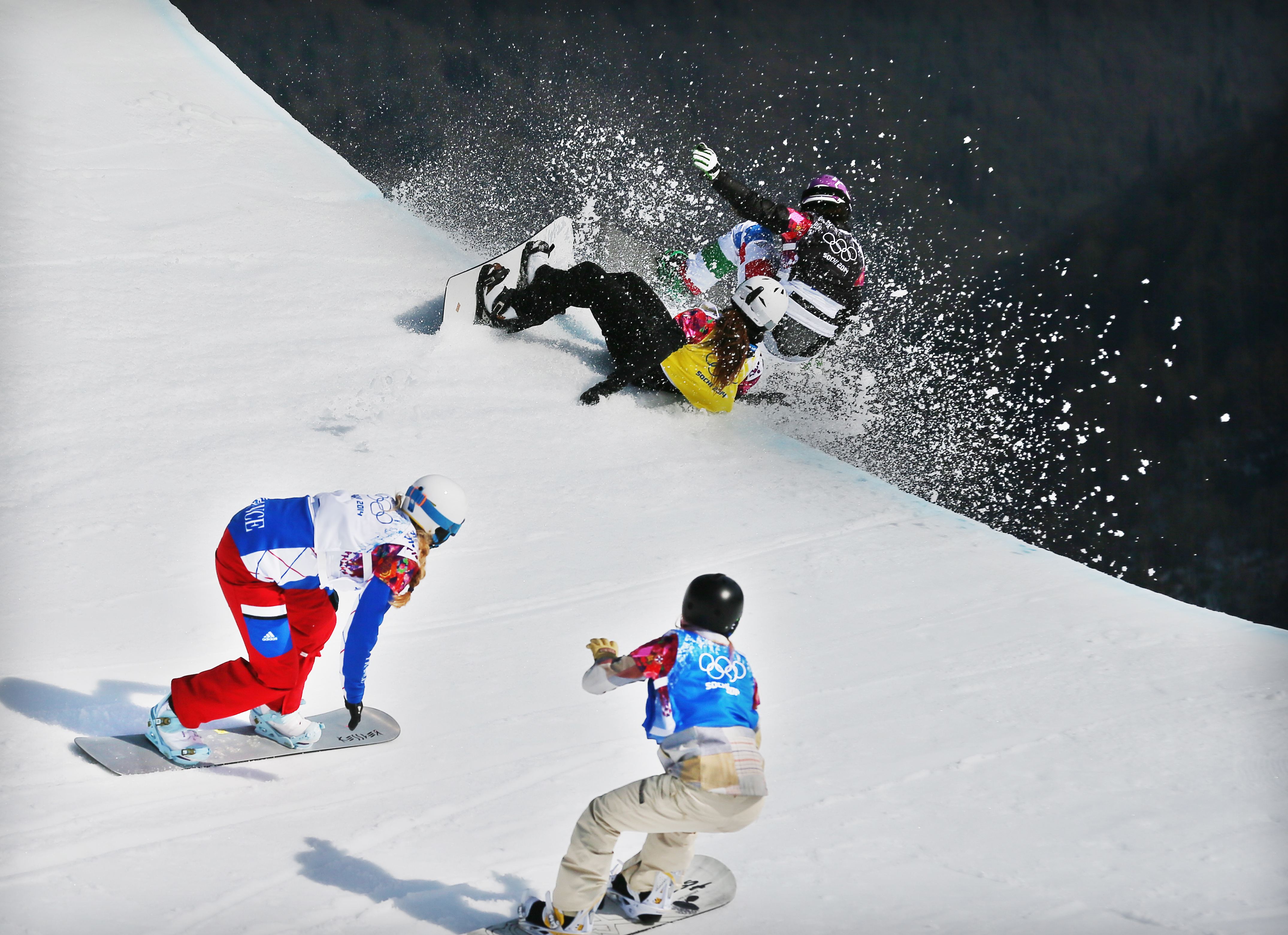 Michela Moioli of Italy (black bib) collides with Alexandra Jekova of Bulgaria (yellow) in front of Chloe Trespeuch of France (white) and Faye Gulini of the USA (blue) during the Women's Snowboard Cross final at Rosa Khutor Extreme Park at the Sochi 2014 Olympic Games, Krasnaya Polyana, Russia, Feb. 16, 2014.
