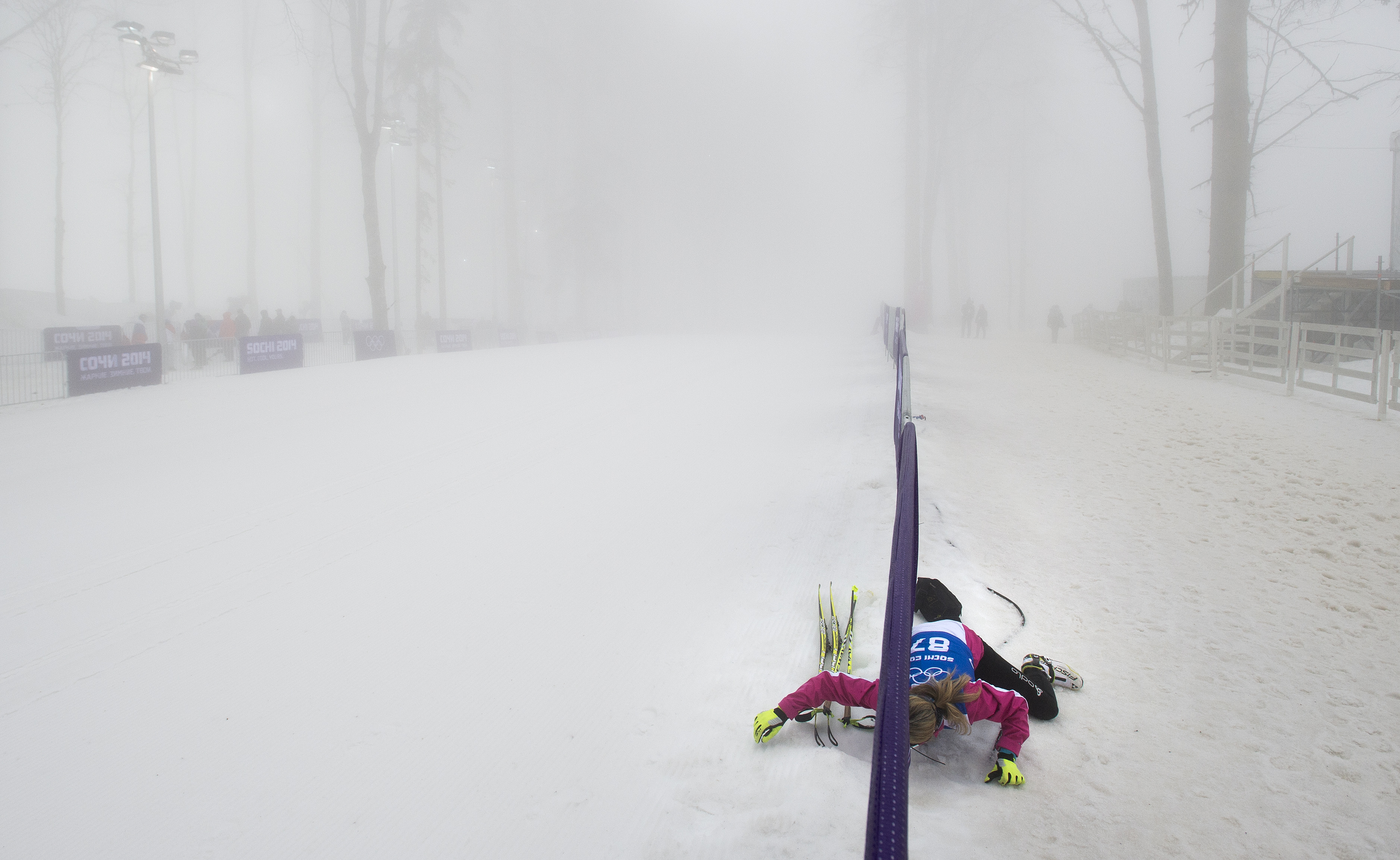 Biathlete Laure Soulie of Andorra crawls under a barricade onto the course to practice in heavy fog during a delay prior to the Men's Biathlon 15km competition at Laura Biathlon Center.