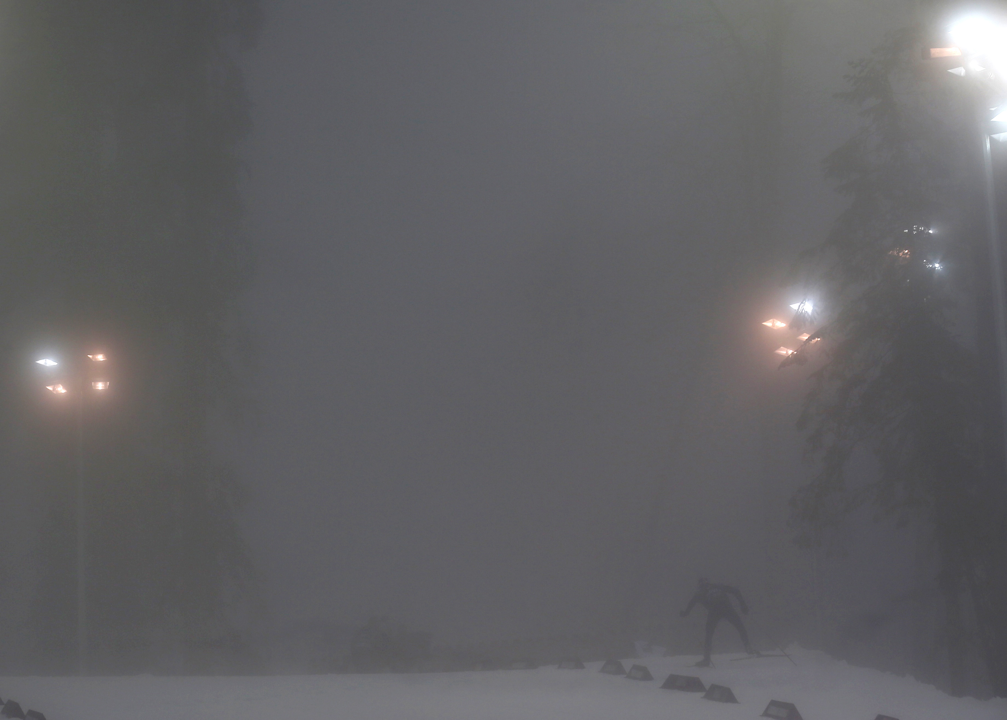 A skier travels amid heavy fog at the Laura Cross Country Ski and Biathlon Center.
