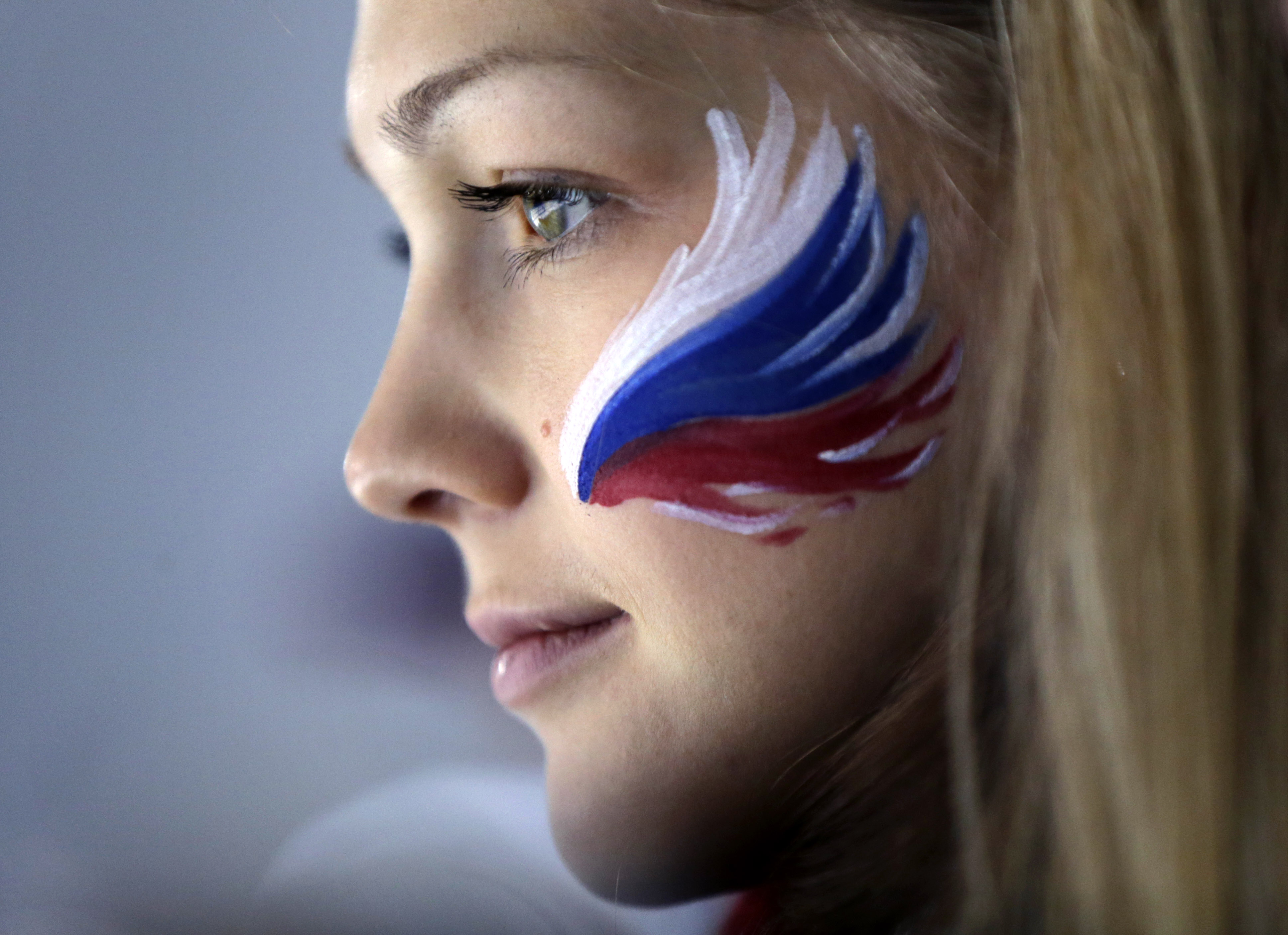A Russian fan wears face paint while attending a men's curling competition.