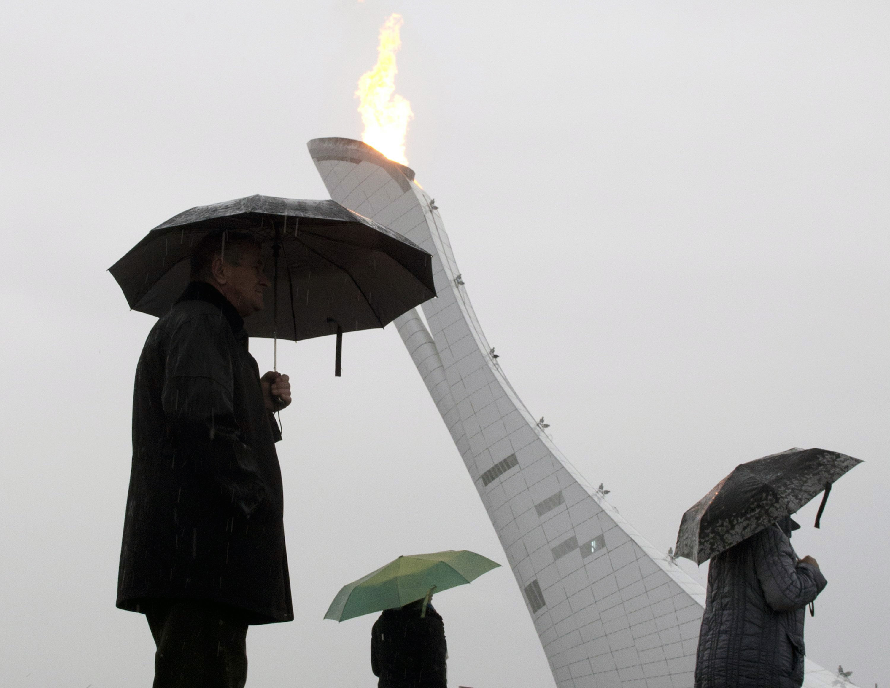 Visitors to the Olympic park walk past the Olympic cauldron as it rains at the Sochi Winter Olympics.