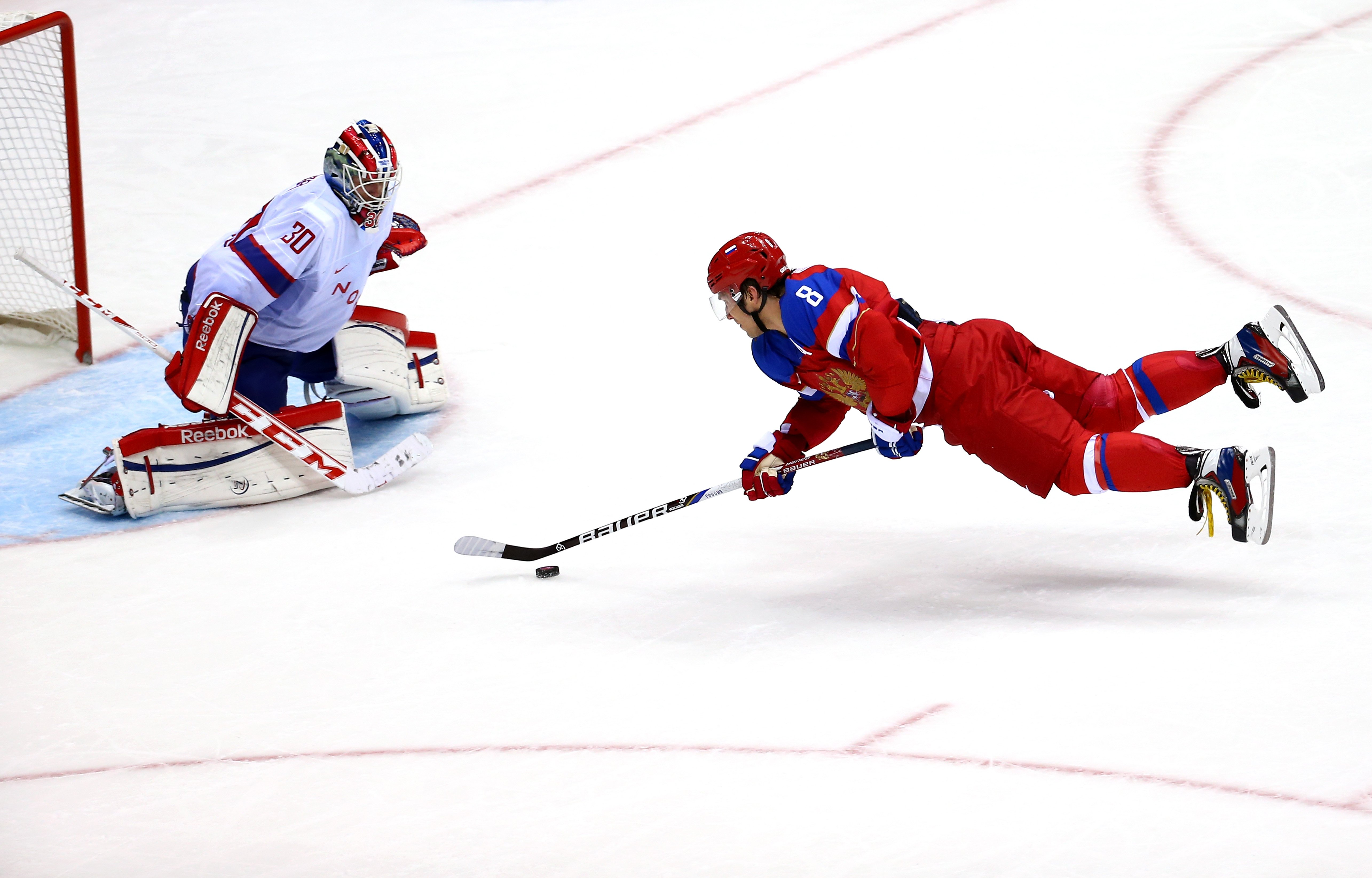 Alexander Ovechkin #8 of Russia falls to the ice against Lars Haugen #30 of Norway during the Men's Ice Hockey Qualification Playoff game.