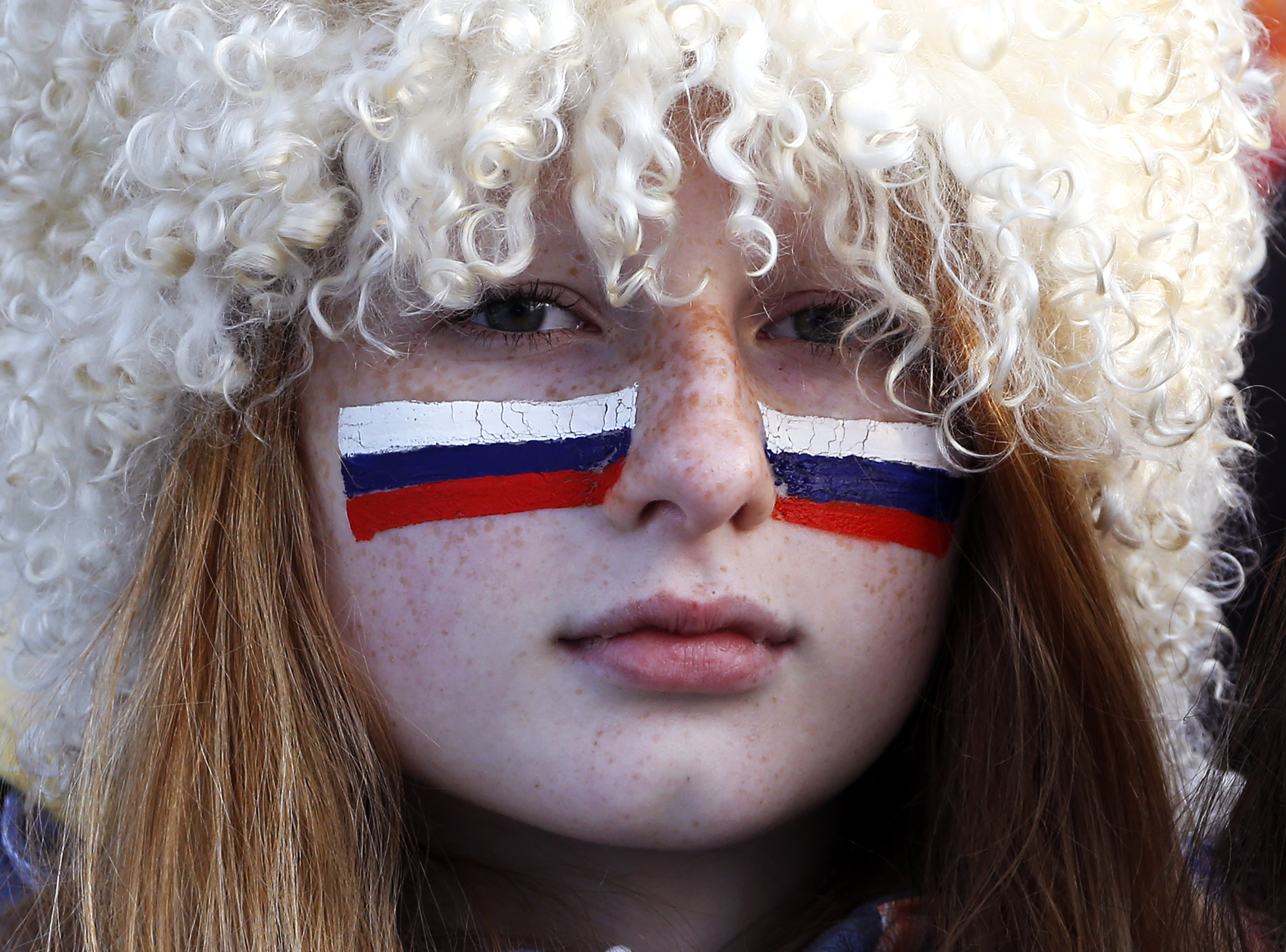 A Russian fan with her face painted with the Russian flag watches the men's quarter-finals ice hockey game between Russia and Finland. Russia was eliminated from the men's ice hockey competition at the Sochi Games on Wednesday following a 3-1 quarter-final loss to Finland.