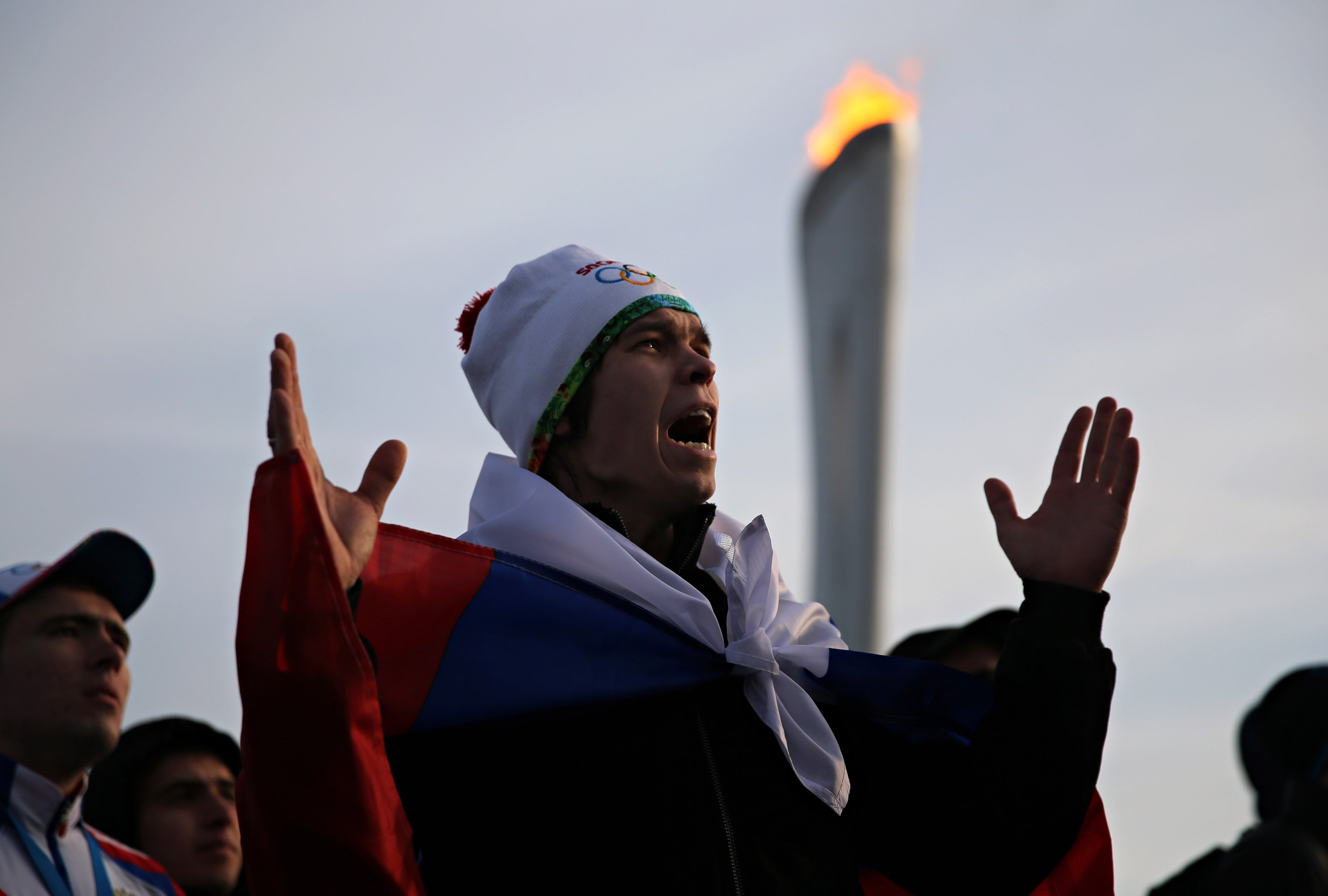A fan wearing a Russian flag in Olympic Park reacts during Russia's 3-1 loss to Finland in men's ice hockey.