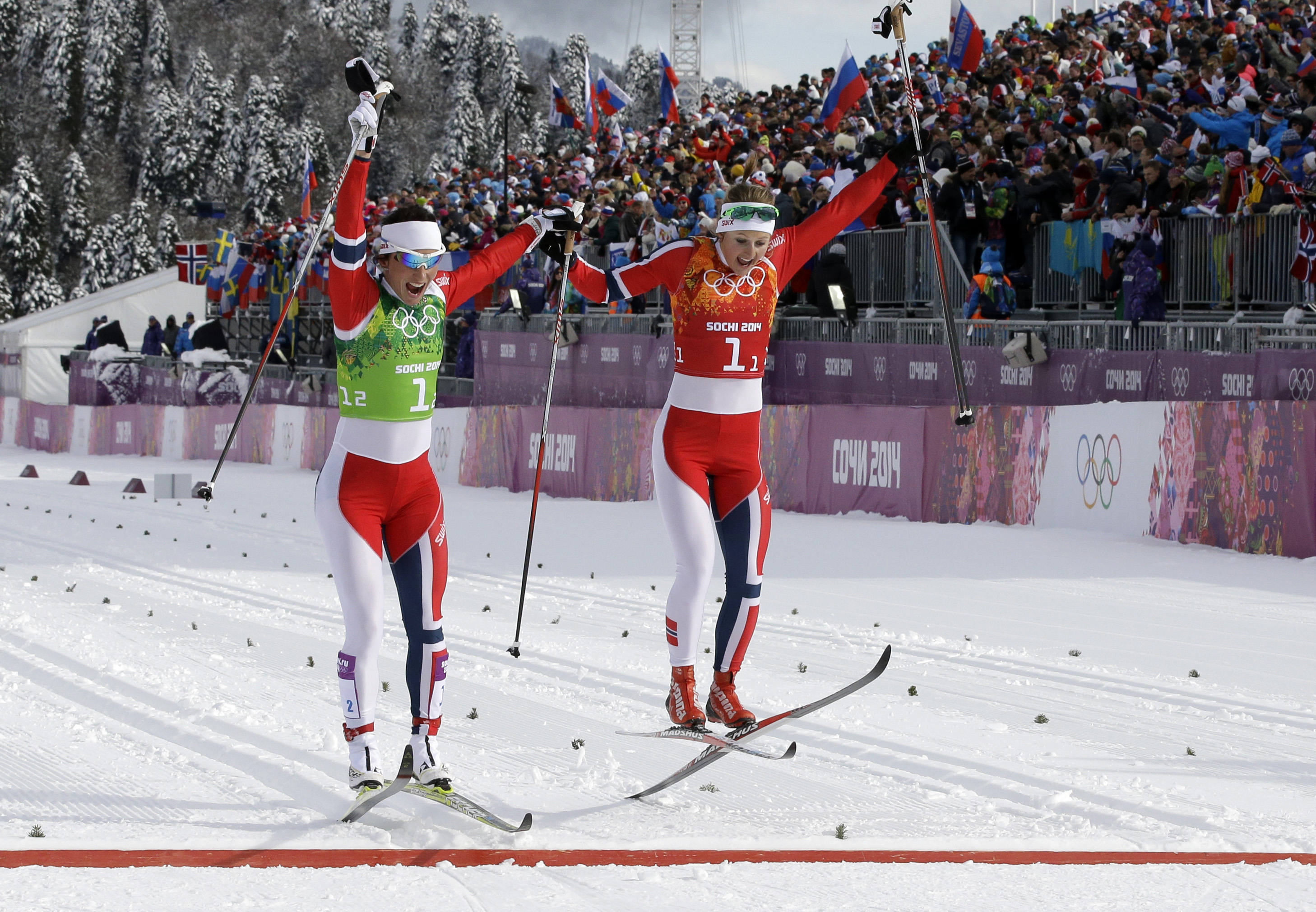 Gold medalists Norway's Marit Bjoergen (L) and Ingvild Flugstad Oestberg celebrate at the finish line in the Women's Cross-Country Skiing Team Sprint Classic Final at the Laura Cross-Country Ski and Biathlon Center.