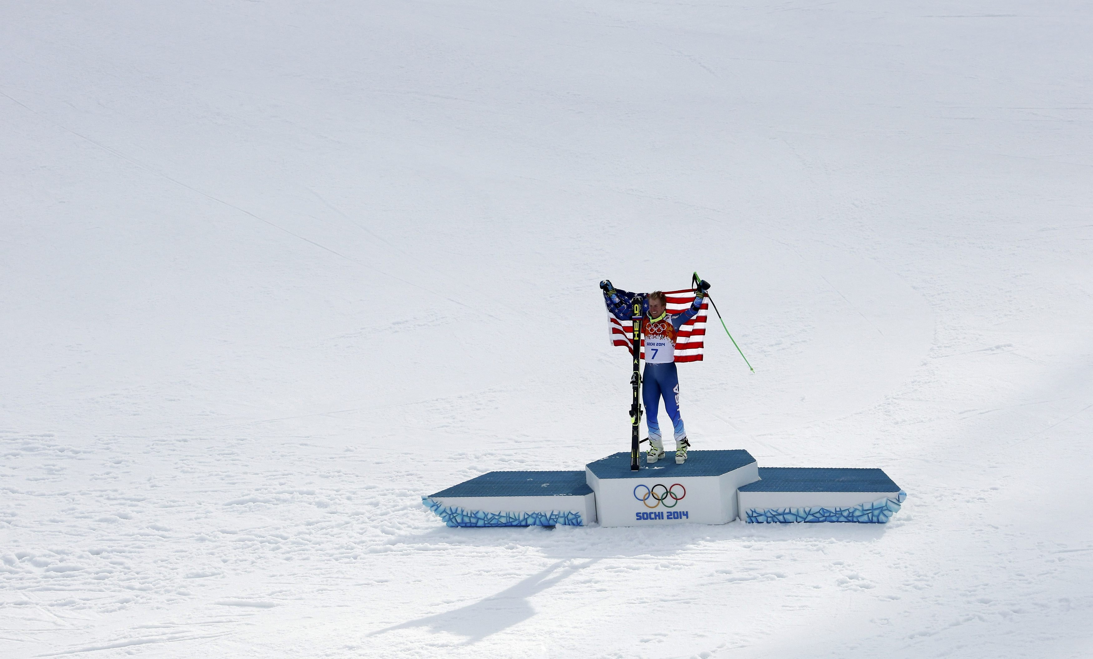Winner Ted Ligety of the U.S. holds up his flag on the podium after the men's alpine skiing giant slalom event.