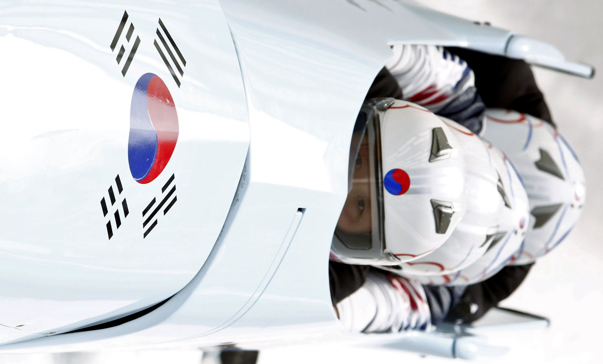 South Korea's pilot Kim Dong-hyun (front) and his teammates speed down the track during a four-man bobsleigh training session at the Sanki Sliding Center.
