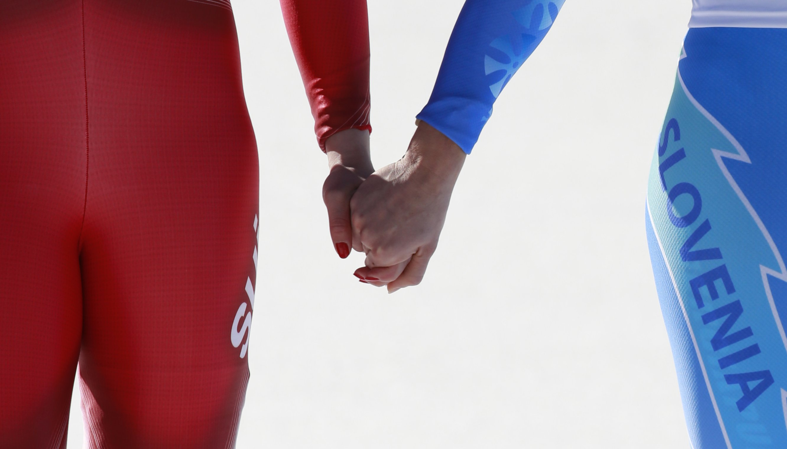 Women's downhill gold medal winners Switzerland's Dominique Gisin, left, and Slovenia's Tina Maze, right, hold hands on the podium during a flower ceremony.