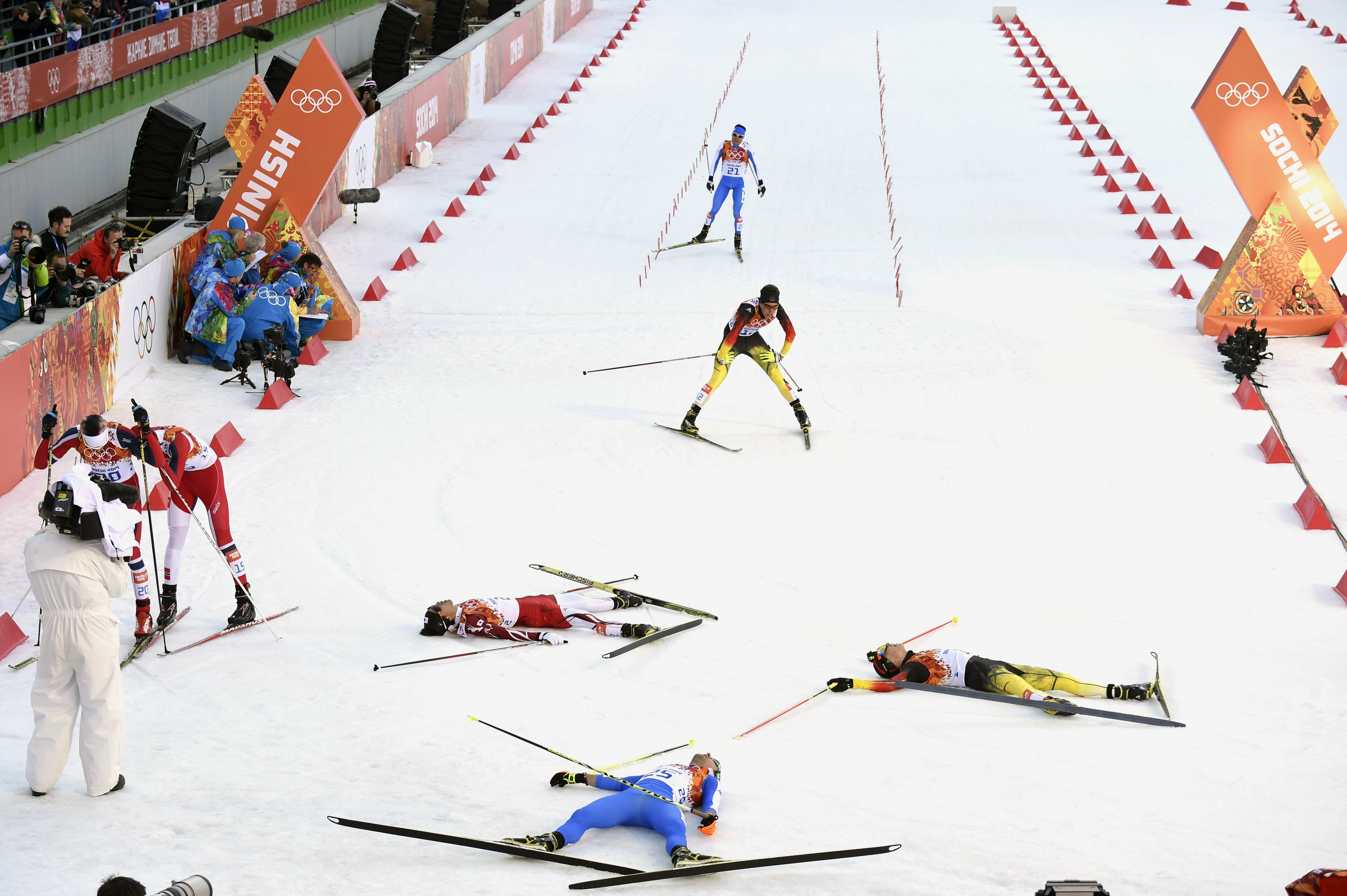 Gold medalist Germany's Eric Frenzel, silver medalist Japan's Akito Watabe and fourth place Italy's Alessandro Pittin lie on the snow at the finish line of the Nordic Combined Individual NH / 10 km Cross-Country.