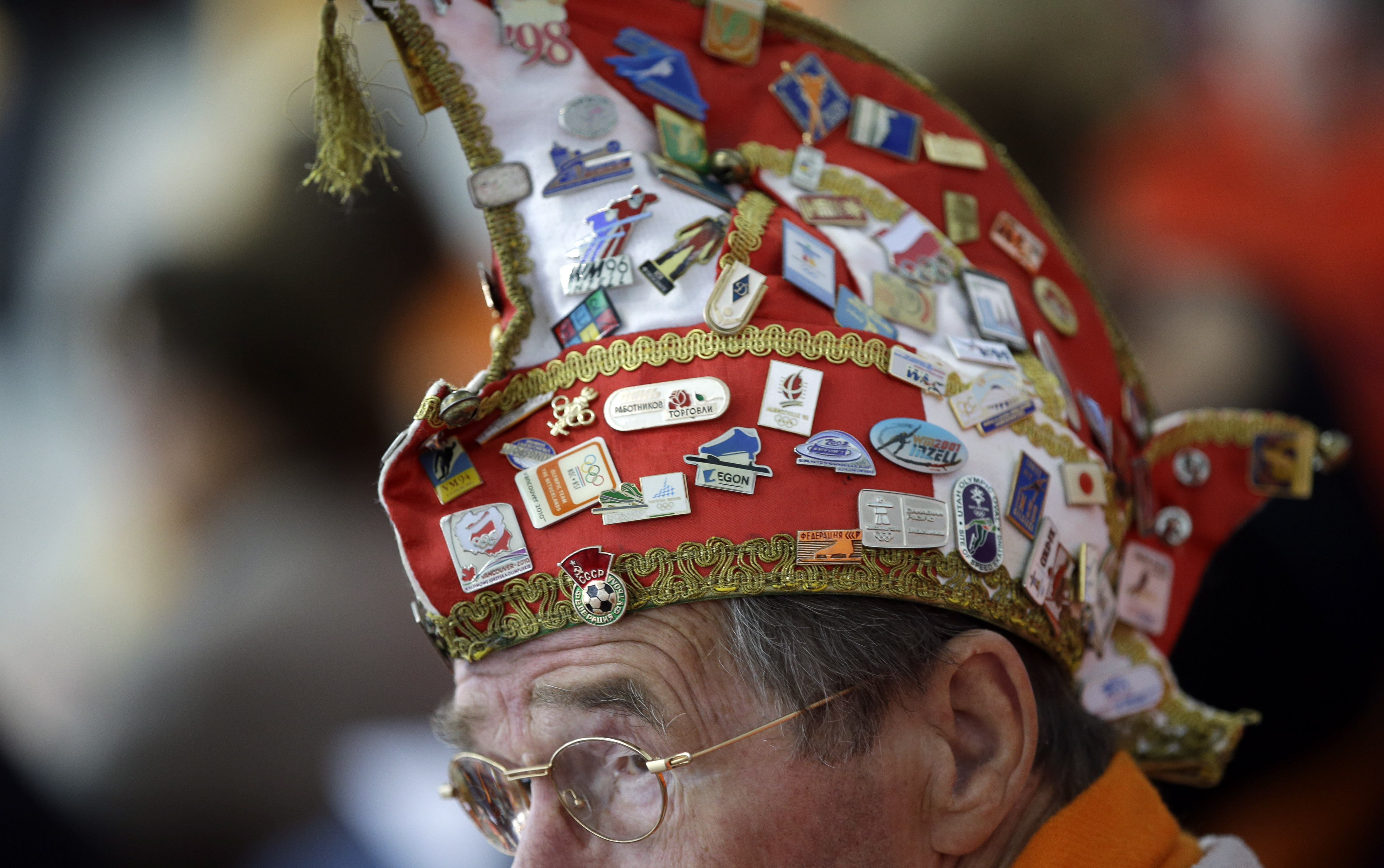 A Dutch skating fan, his hat filled with Olympic pins, watches the women's 1,000-meter speedskating race.