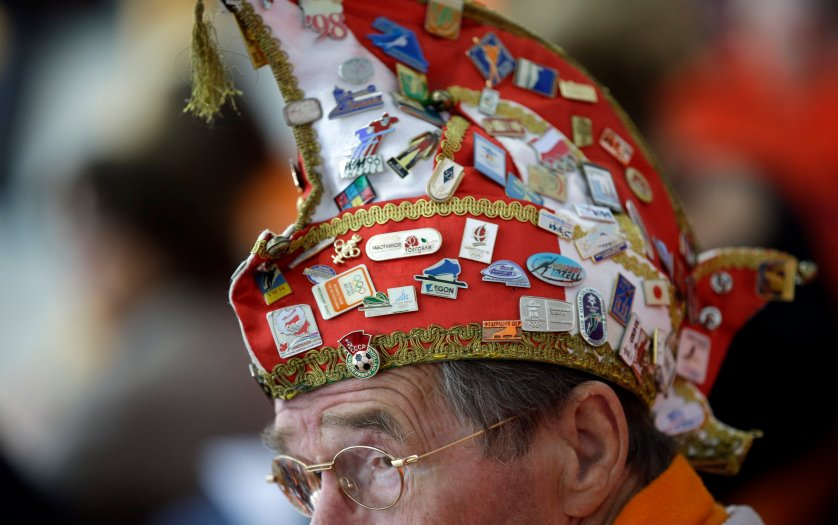 A Dutch skating fan, his hat filled with Olympic pins, watches the women's 1,000-meter speedskating race during the 2014 Winter Olympics in Sochi, Russia, Feb. 13, 2014.