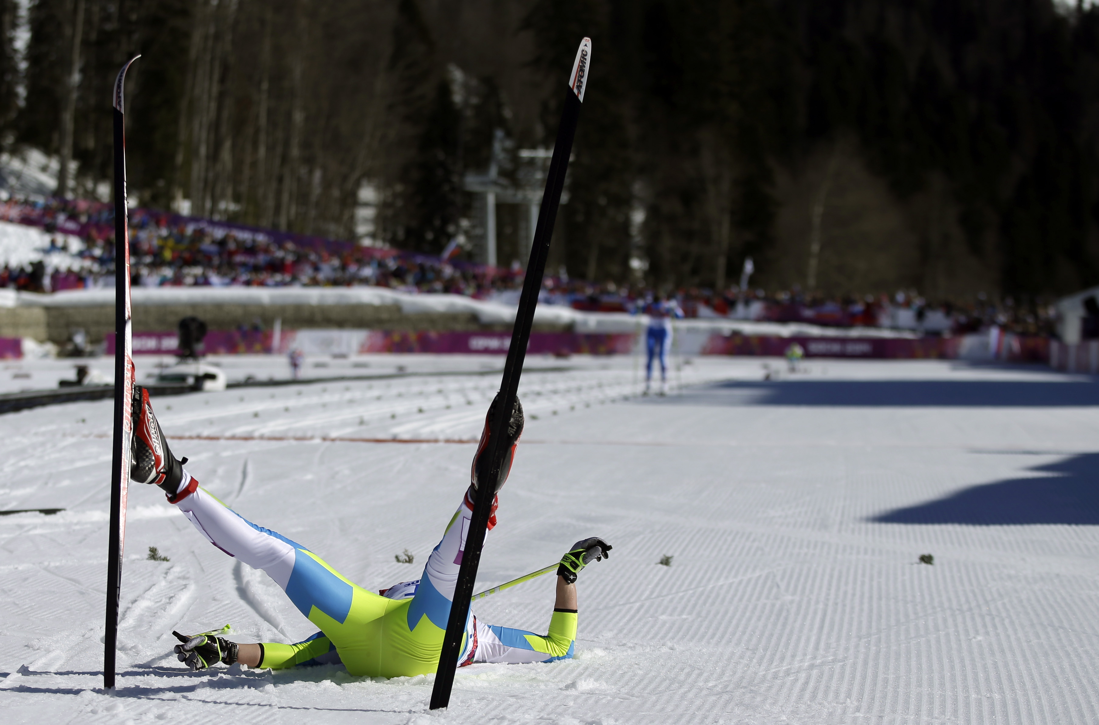 Slovenia's Barbara Jezersek lies on the snow after completing the women's 10K classical-style cross-country race.