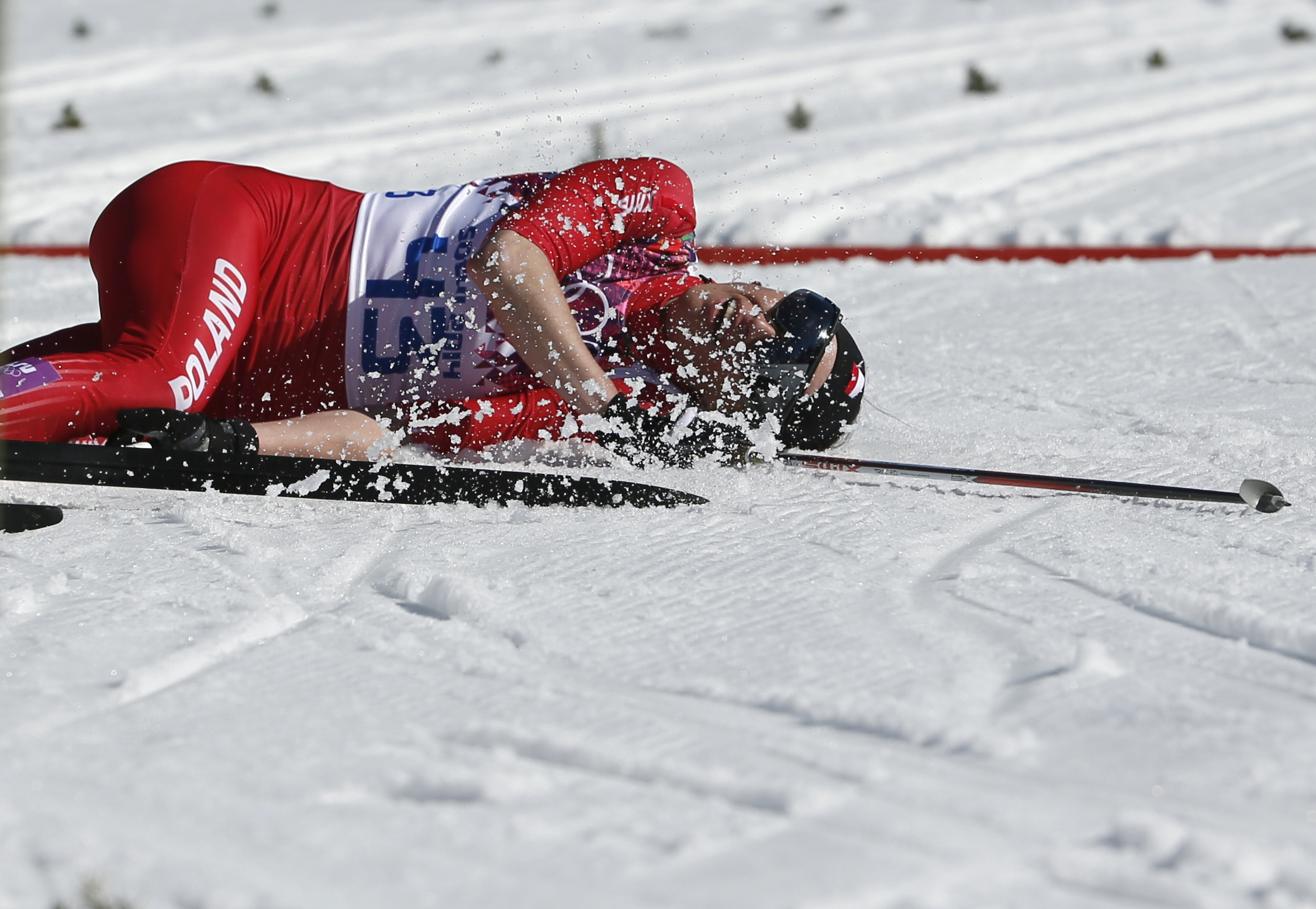 Poland's Justyna Kowalczyk lies on the ground after crossing the finish line in the women's cross-country 10km classic event.