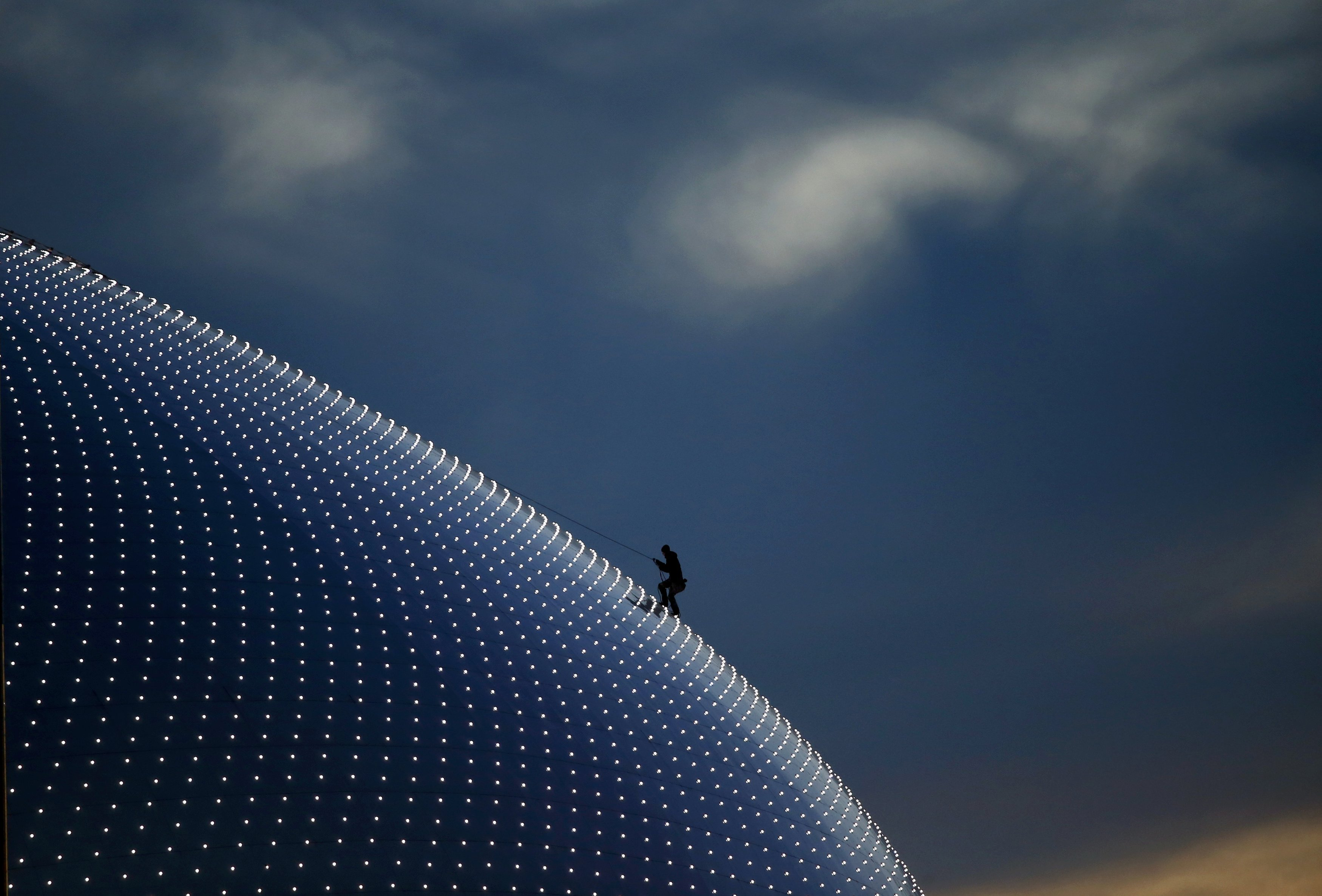 A person climbs on the Bolshoi Dome, one of the ice hockey venues, before the medals ceremony.