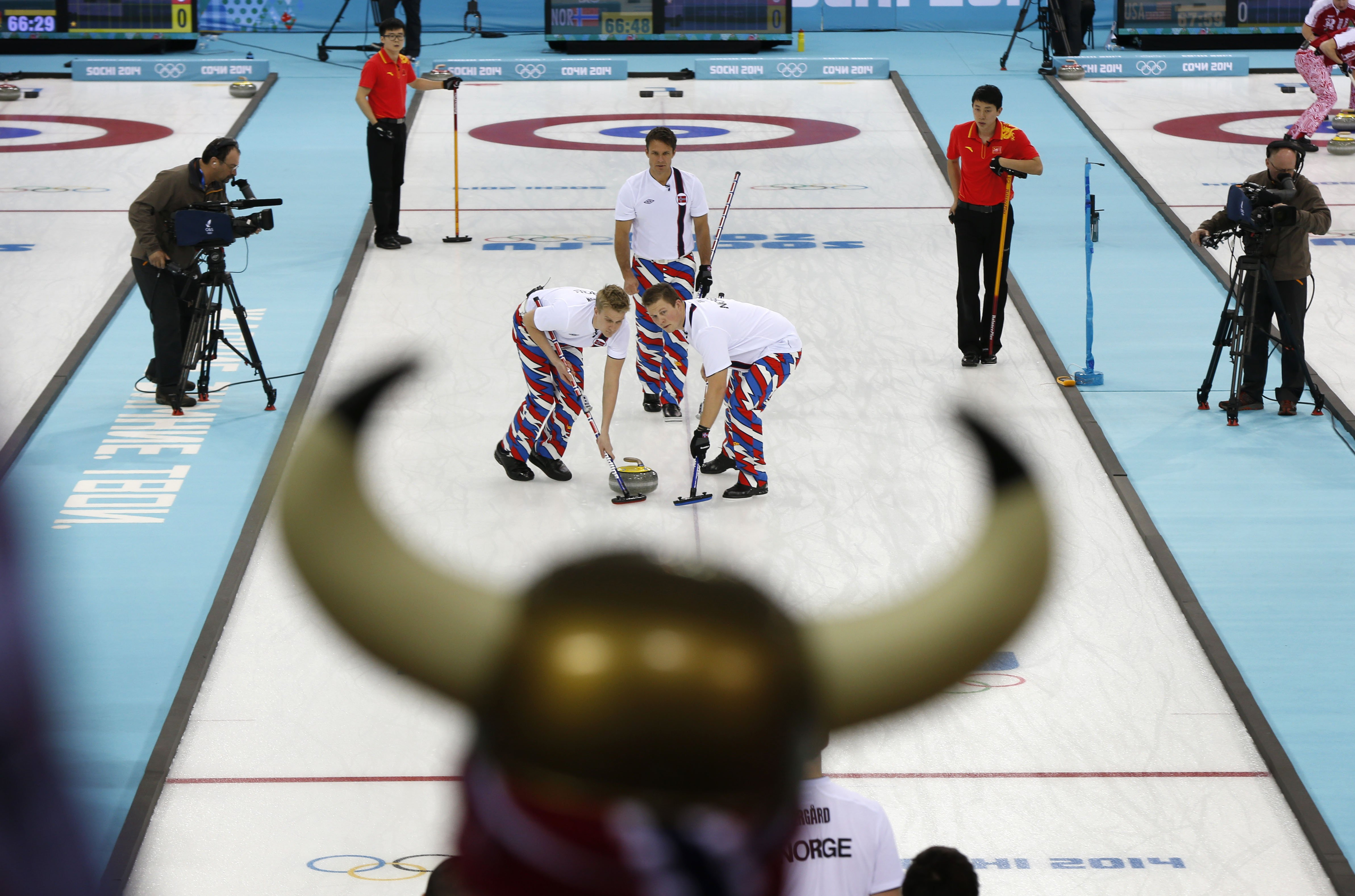 Norwegian curling fan Rune Eikeland, wearing viking horns, watches his countrymen Haavard Vad Petersson, left, and Christoffer Svae sweep in front of a rock delivered by skip Thomas Ulsrud during the men's curling competition against China.