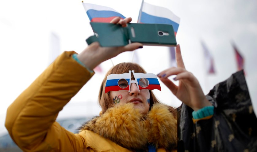 A woman sports the Russian national flag with her eyewear and takes photographs with a smart phone at Olympic Park.