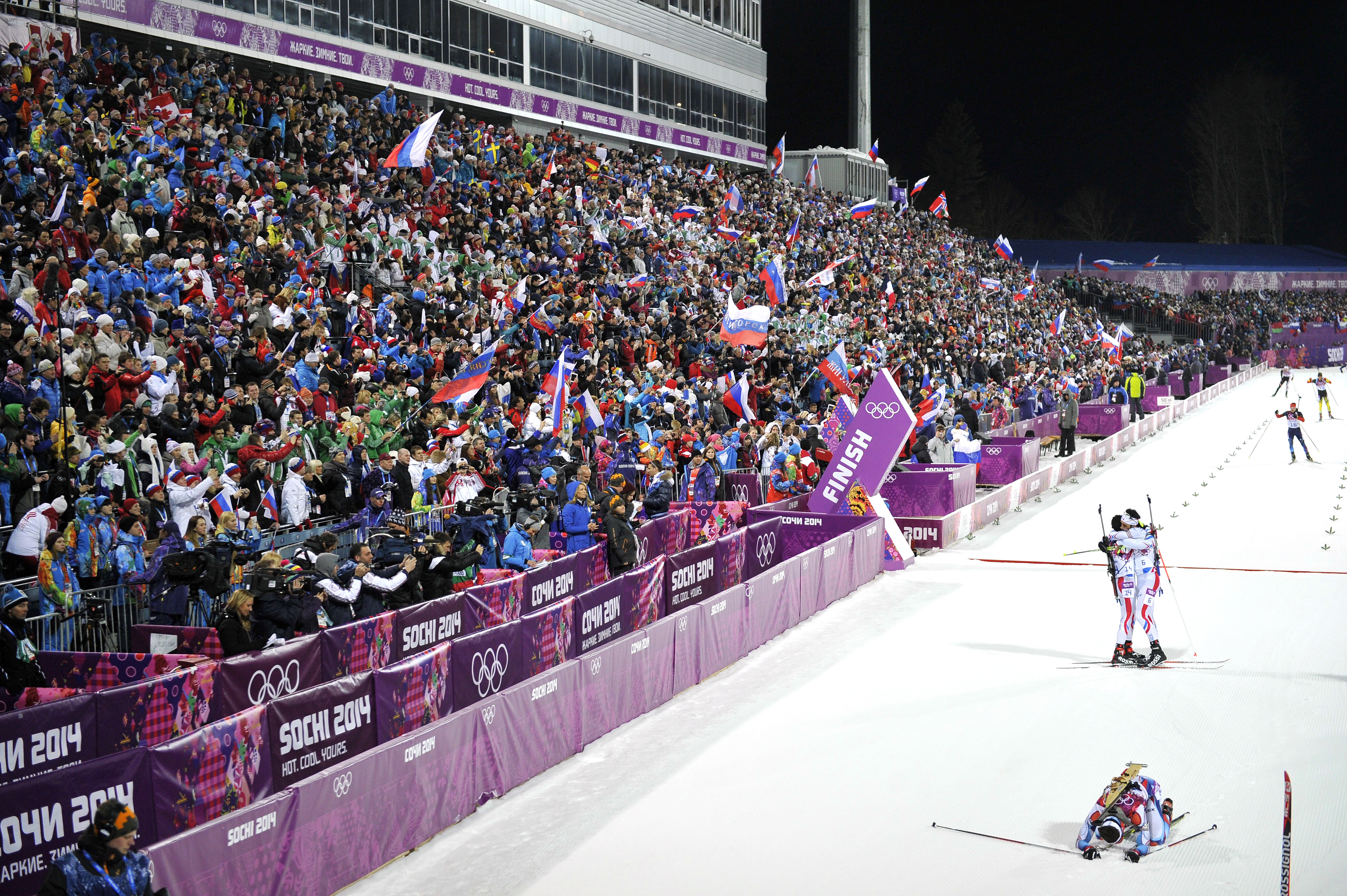 Gold medalist Martin Fourcade and bronze medalist Jean Guillaume Beatrix, both of France, celebrate while silver medalist Ondrej Moravec of the Czech Republic lies on the ground in the finish area of the Biathlon Men's 12.5km Pursuit at the Laura Cross-country Ski & Biathlon Center.