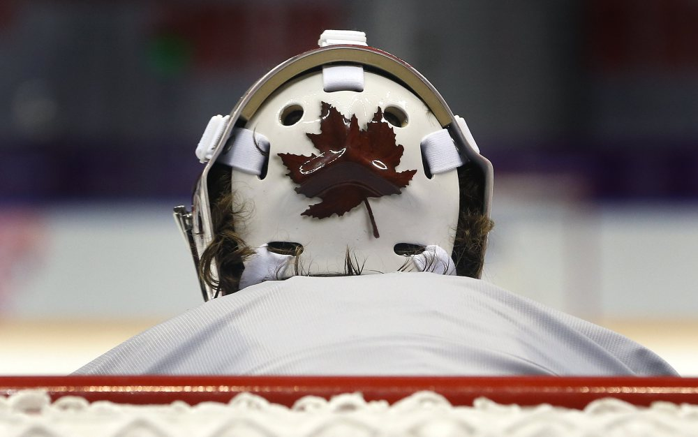 Canada goaltender wears a helmet decorated with a Canadian maple leaf during a training session.