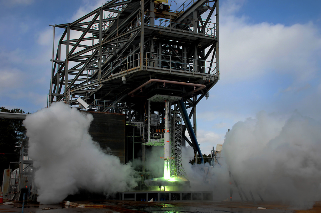A 5-percent scale model of NASA's planned heavy-lift rocket, which will be used for launching astronauts, is ignited for five seconds to measure the effects noise and pressure have on the vehicle at liftoff, on Jan. 28, 2014. The green flame is a result of the ignition fluid that is burned along with the propellant during this short-duration test.