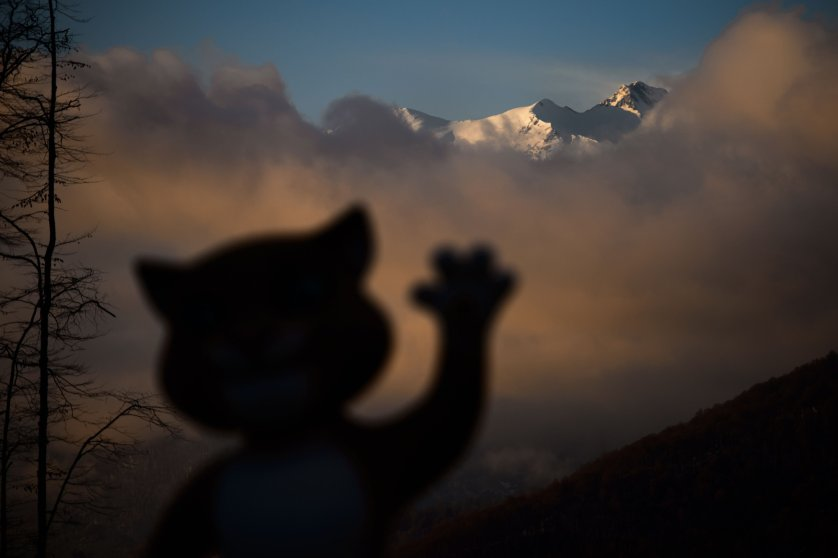 A mascot of Sochi Winter Olympics is seen in silhouette with mountains at sunset at the Mountain athletes village during the Sochi Winter Olympics on Feb. 11, 2014.