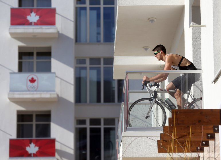A member of the Canadian team takes advantage of warm weather to work out on his balcony in Olympic Village at the Winter Olympics in Sochi, Russia, Thursday, Feb. 6, 2014.