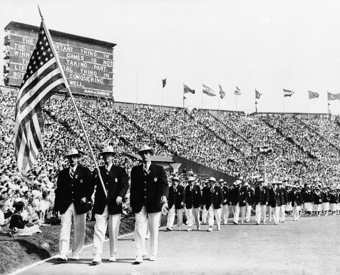 Yachter Ralph Craig, center, of Albany, N.Y., carries the American flag in the parade of the nations at the opening of the summer Olympic games in London's Wembley Stadium, July 29, 1948.