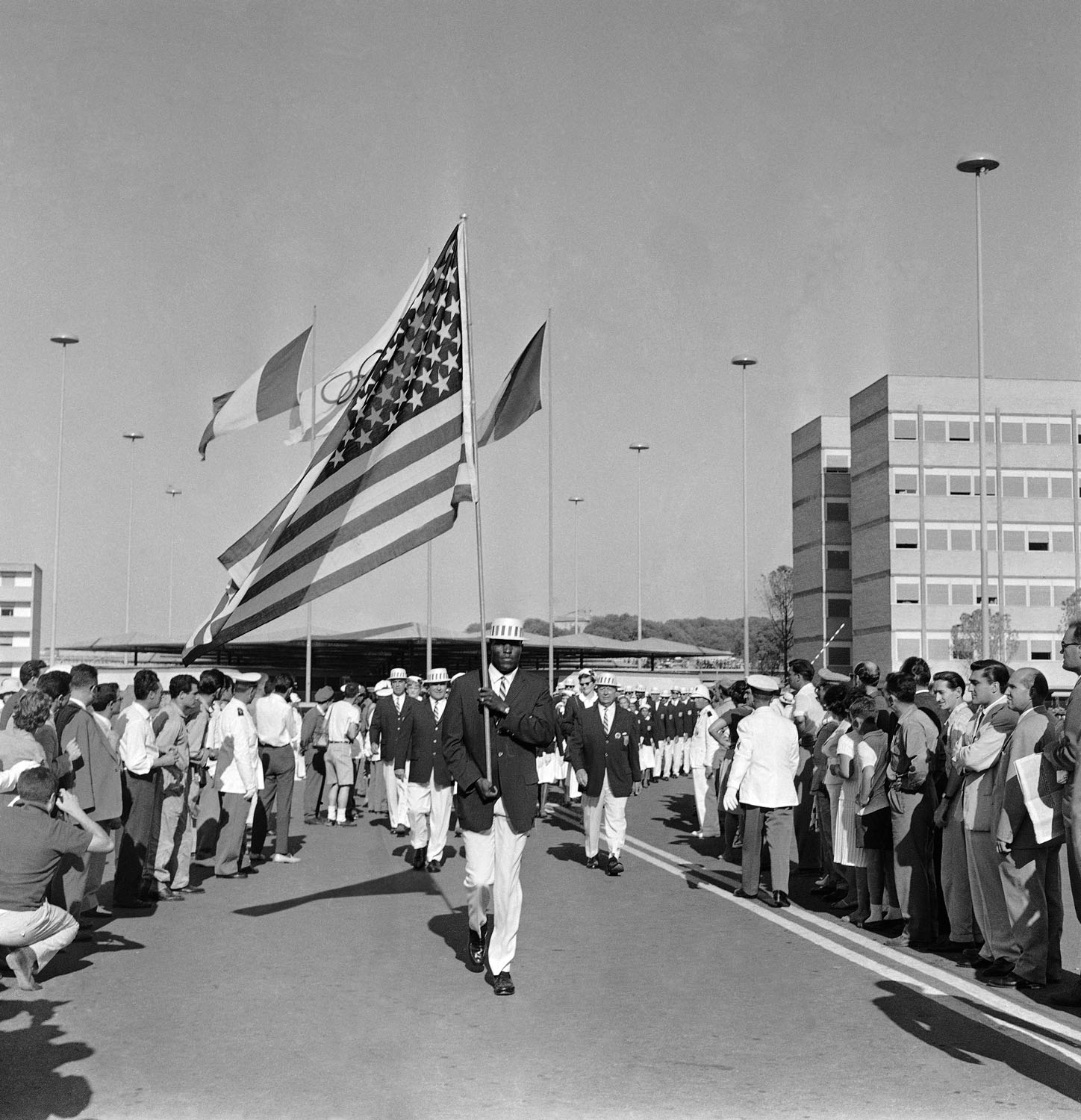 Track and Field athlete Rafer Johnson carries the American flag while leading his team out of the Olympic Village to march in the opening ceremony of the Rome Summer Olympics in 1960.