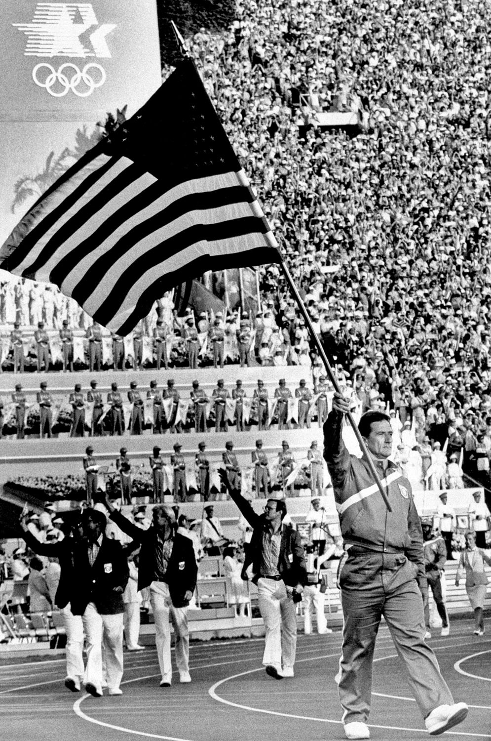 Ed Burke, a hammer thrower, bears the flag of the United States, as the team marches into the Coliseum, during the opening ceremonies of the 23rd Summer Olympics in Los Angeles, July 28, 1984.