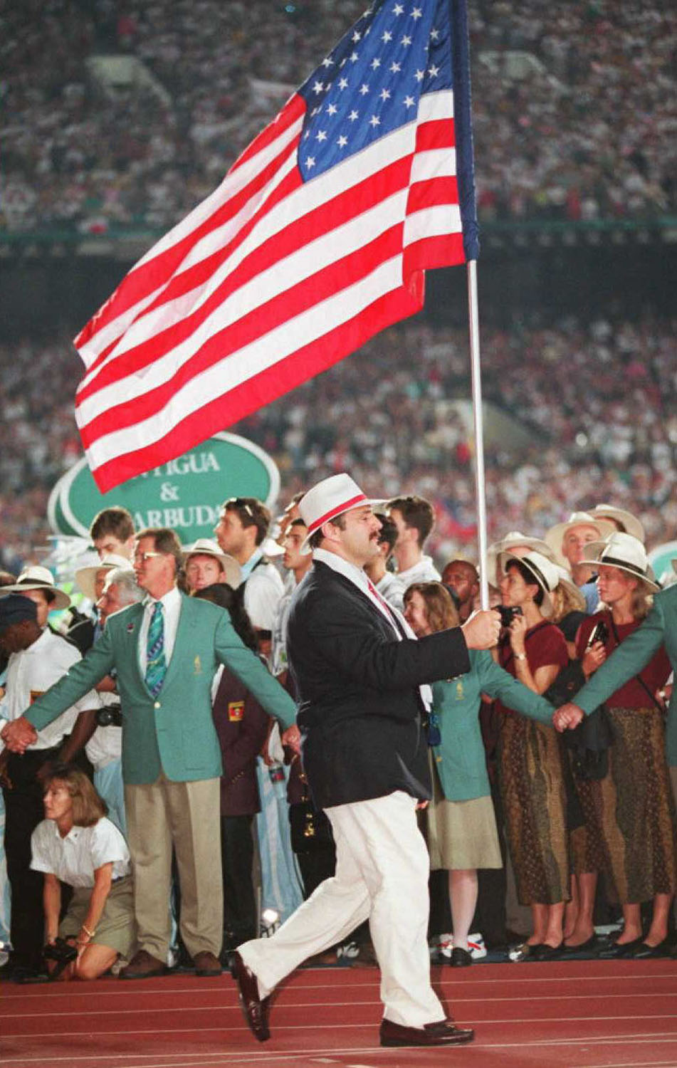 US Olympic wrestler Bruce Baumgartner carries the American flag during the opening ceremony at the Olympic Stadium in Atlanta in 1996.